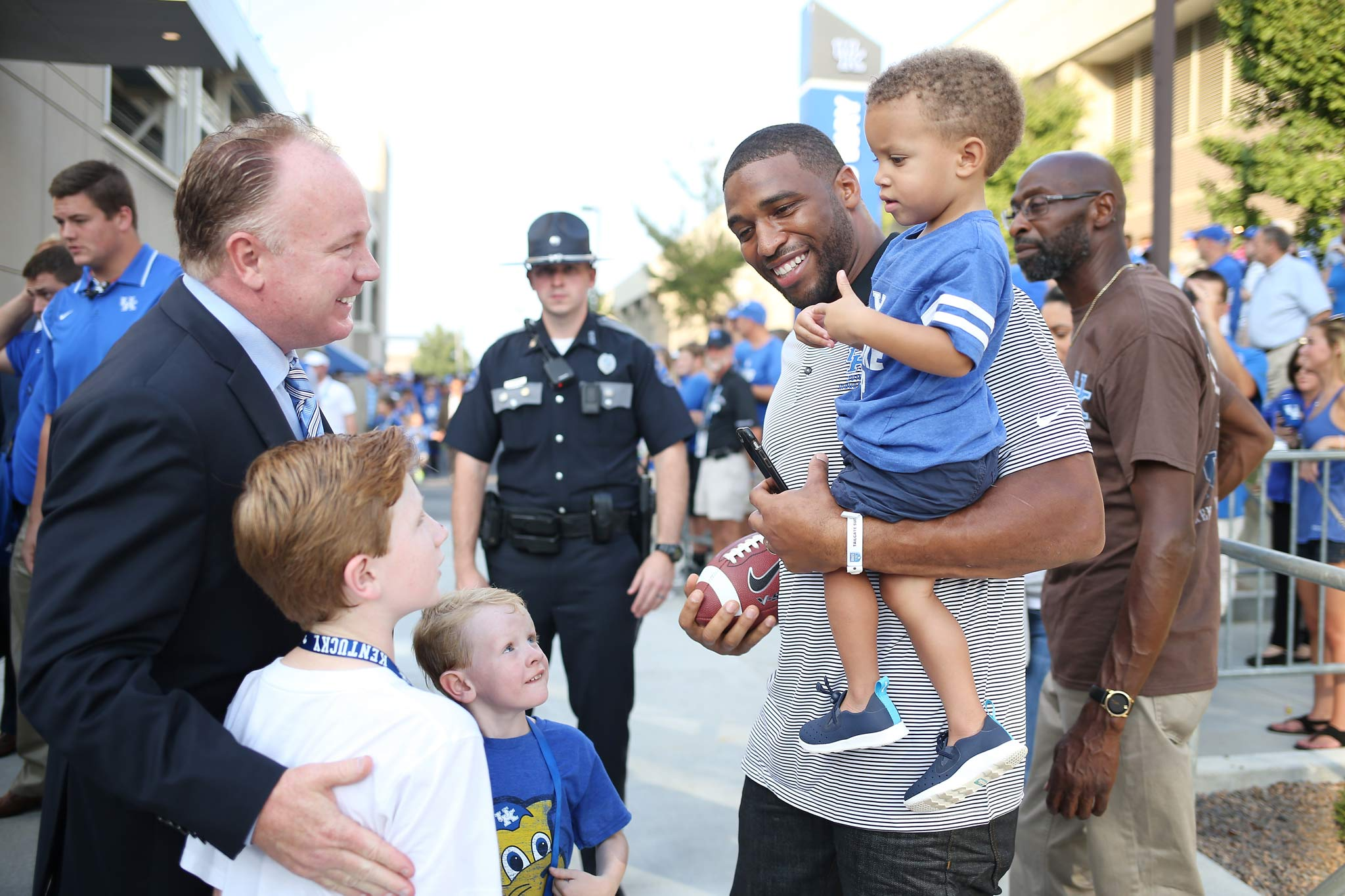 Coach Stoops and his two sons talk with Wesley Woodyard, a former UK linebacker, who is carrying a little boy in his arms.