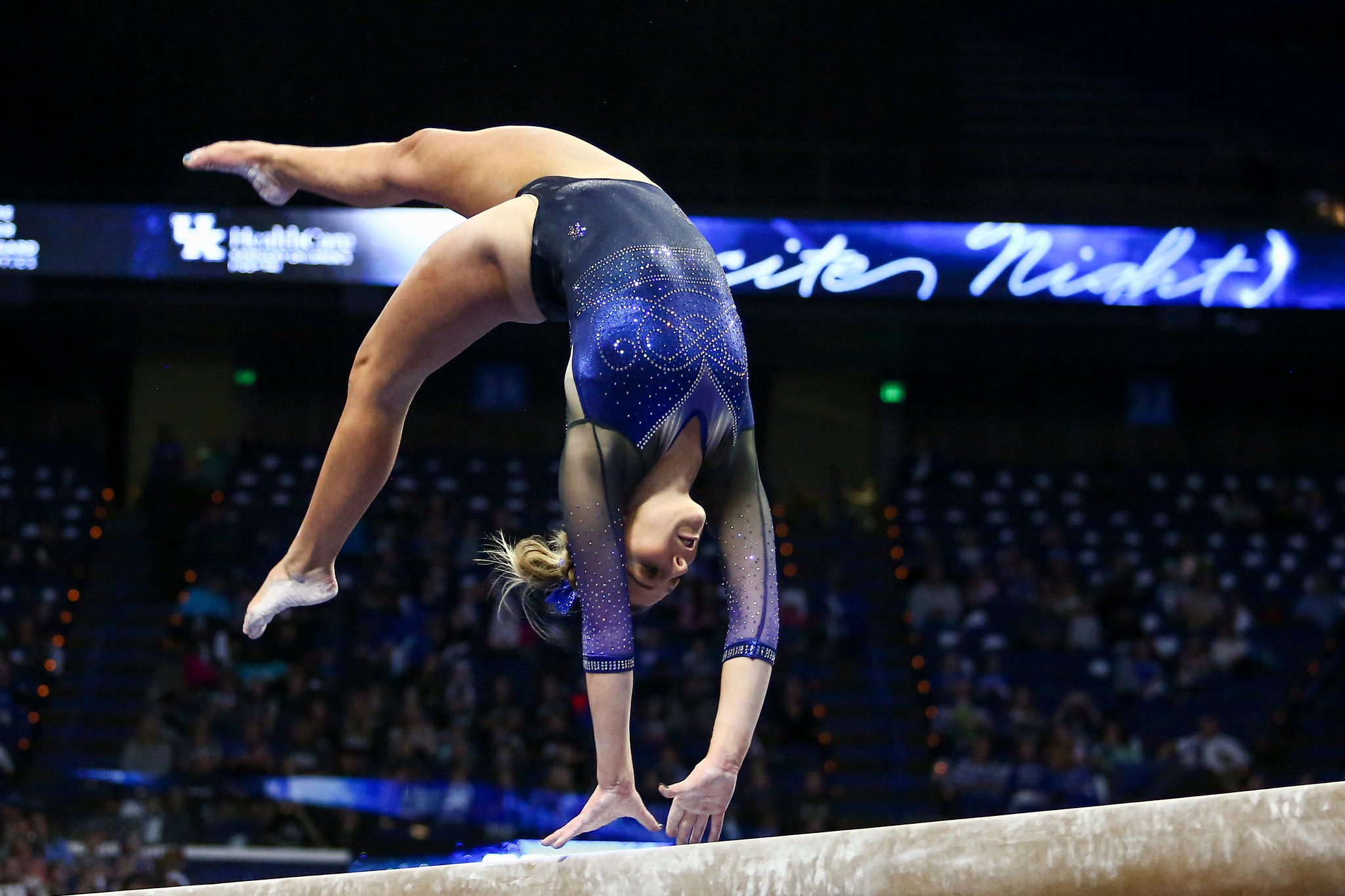 Mac flips backwards atop a balance beam, wearing a sparkly black and blue leotard and a blue bow in her hair.