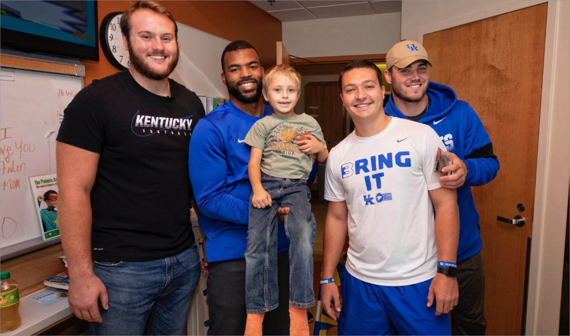 Courtney and three football players visit with a young patient at Kentucky Children's Hospital. Courtney is holding the patient, a little boy, in his arms