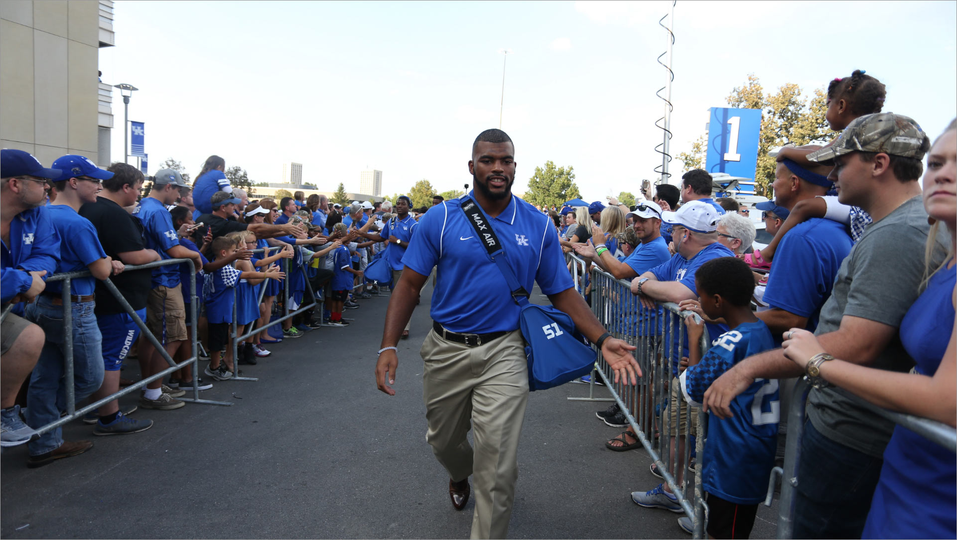 Courtney, wearing a blue polo shirt, walks down the center of two barriers with UK fans behind them. He holds out his hand to give a little boy a high five.