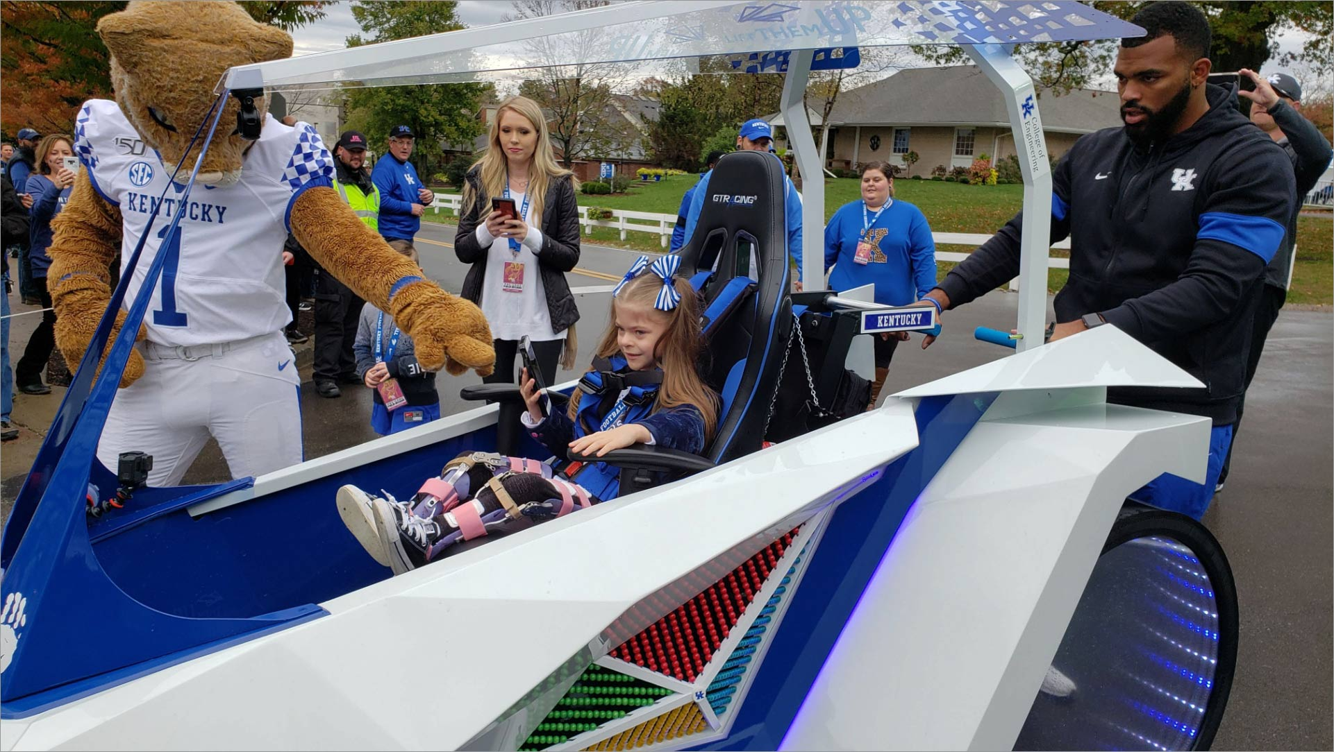 Courtney and the Wildcat mascot surround a little girl in a futuristic-looking blue and white cart. The girl has her hair in pigtails and has pink and purple leg braces.