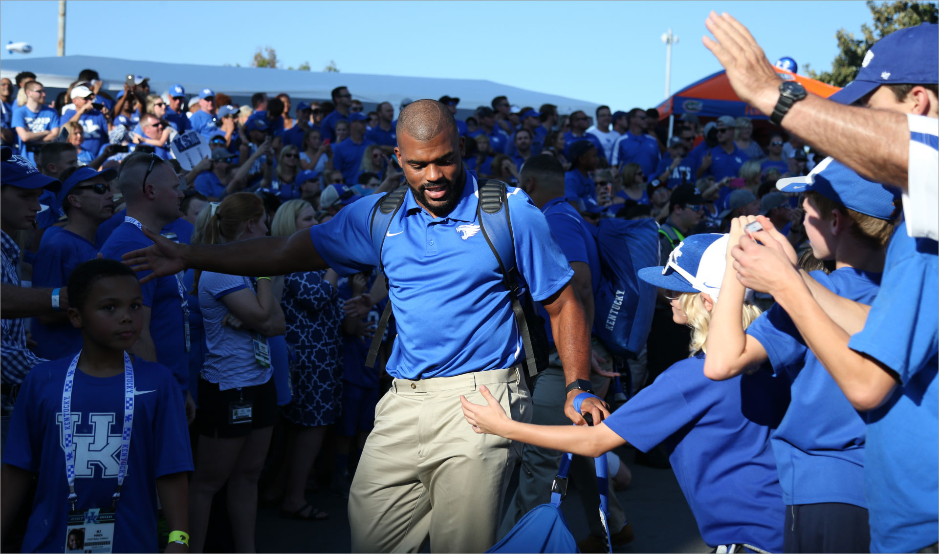 Courtney walks through a crowd of fans, all wearing blue, before a football game. He holds his arm out to give a kid a high five.