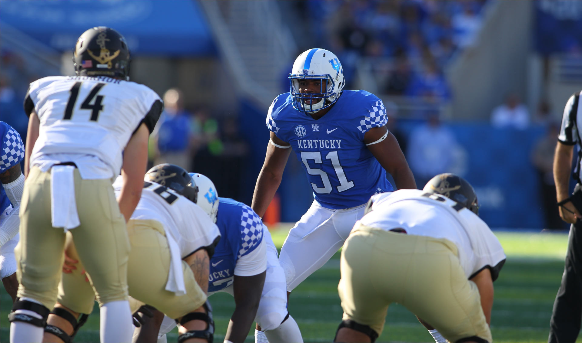 In a photo from his college football days, Courtney stands behind the line of scrimmage, wearing a blue Kentucky jersey with #51 on it.