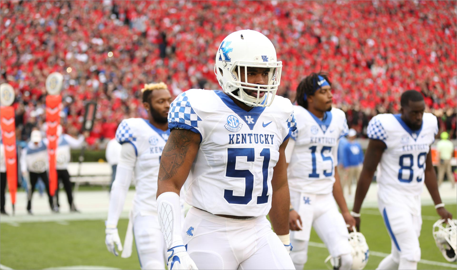 In another photo from his college football days, Courtney walks onto the field with his team. He is wearing a helmet and a white Kentucky jersey with #51 on it.