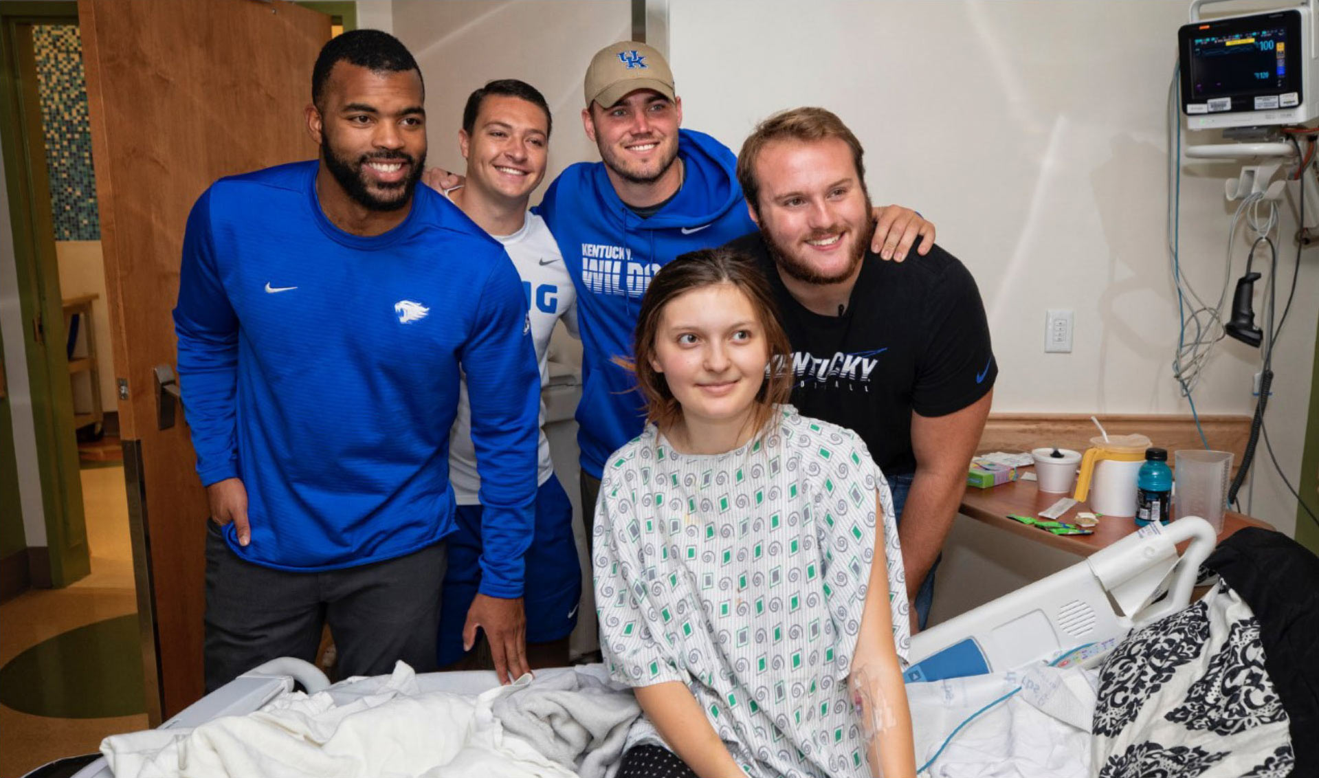 Courtney Love, wearing a blue shirt, and three current football players wearing Kentucky gear, pose with a Kentucky Children's Hospital patient. The patient, a young girl, is sitting in her bed and wearing a hospital gown.