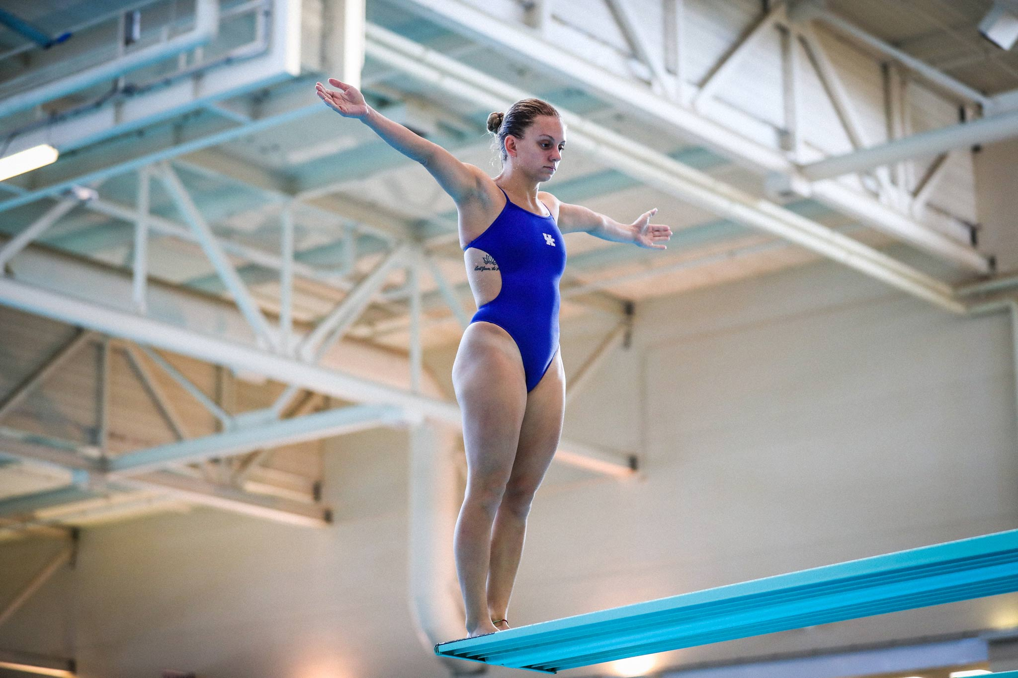 Emma stands on a balance beam during practice. She has her arms out and is wearing a blue UK swimsuit.