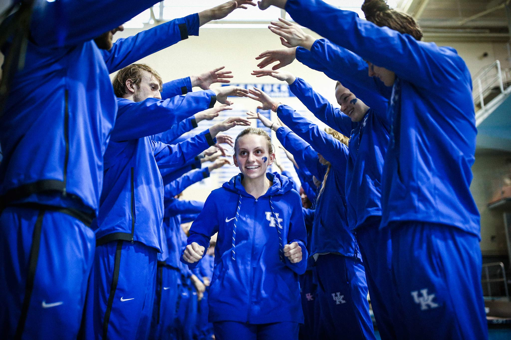 Emma, wearing a blue UK hoodie, runs between two rows of swimmers, all dressed in blue. They have their arms out, forming an arch that she's running through.
