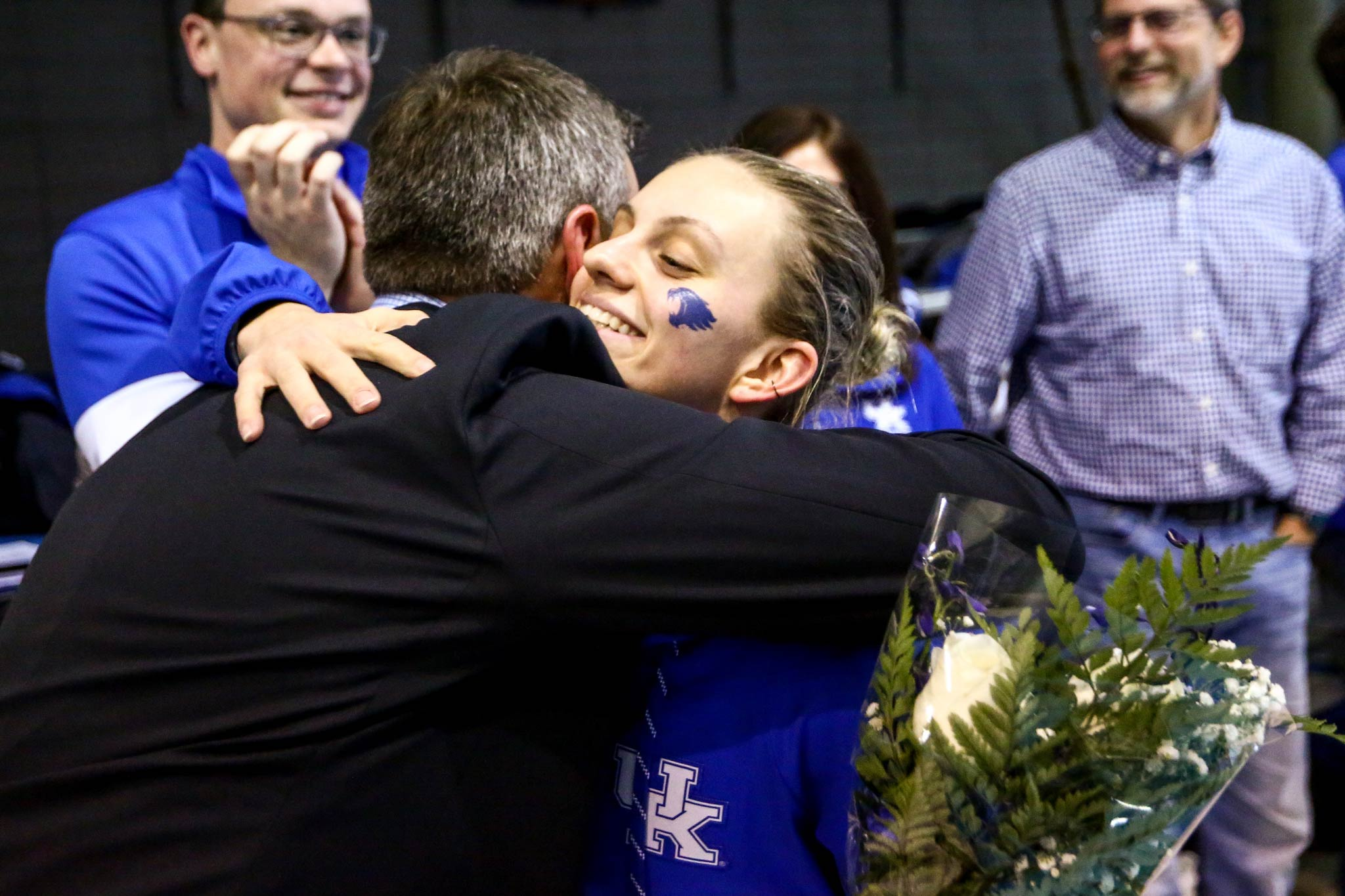 Emma, with a small blue Wildcat head painted on her cheek, hugs a man wearing a suit. She is holding a bouquet of flowers. People in the background are applauding.