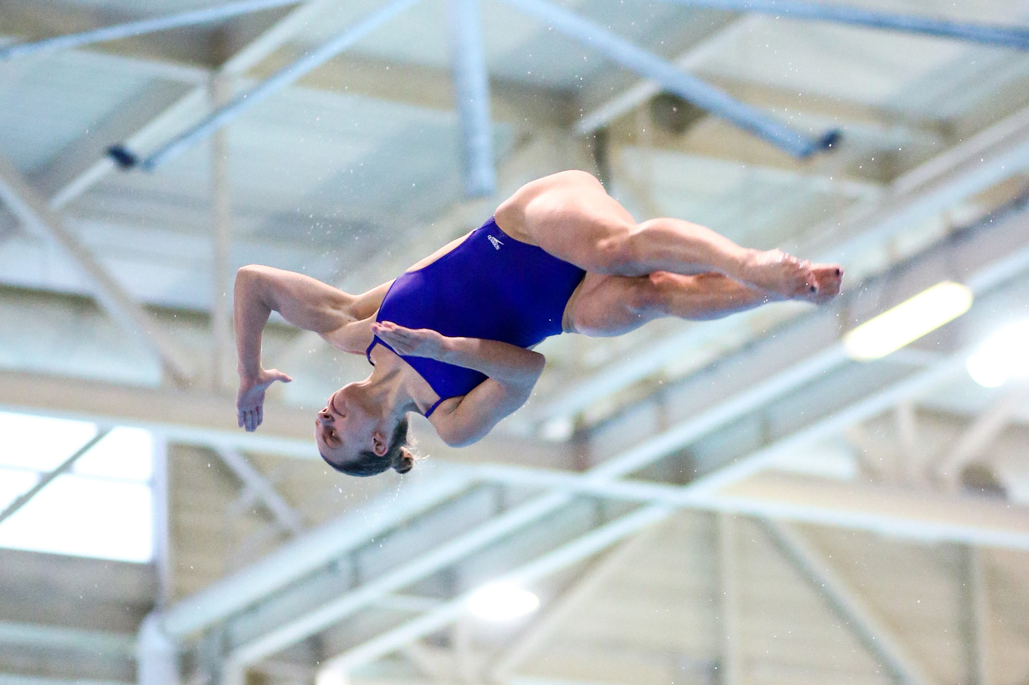 Emma is mid-dive, wearing a blue one-piece swimsuit. She is midair, turning sideways and twisting with her legs straight out and her toes pointed.