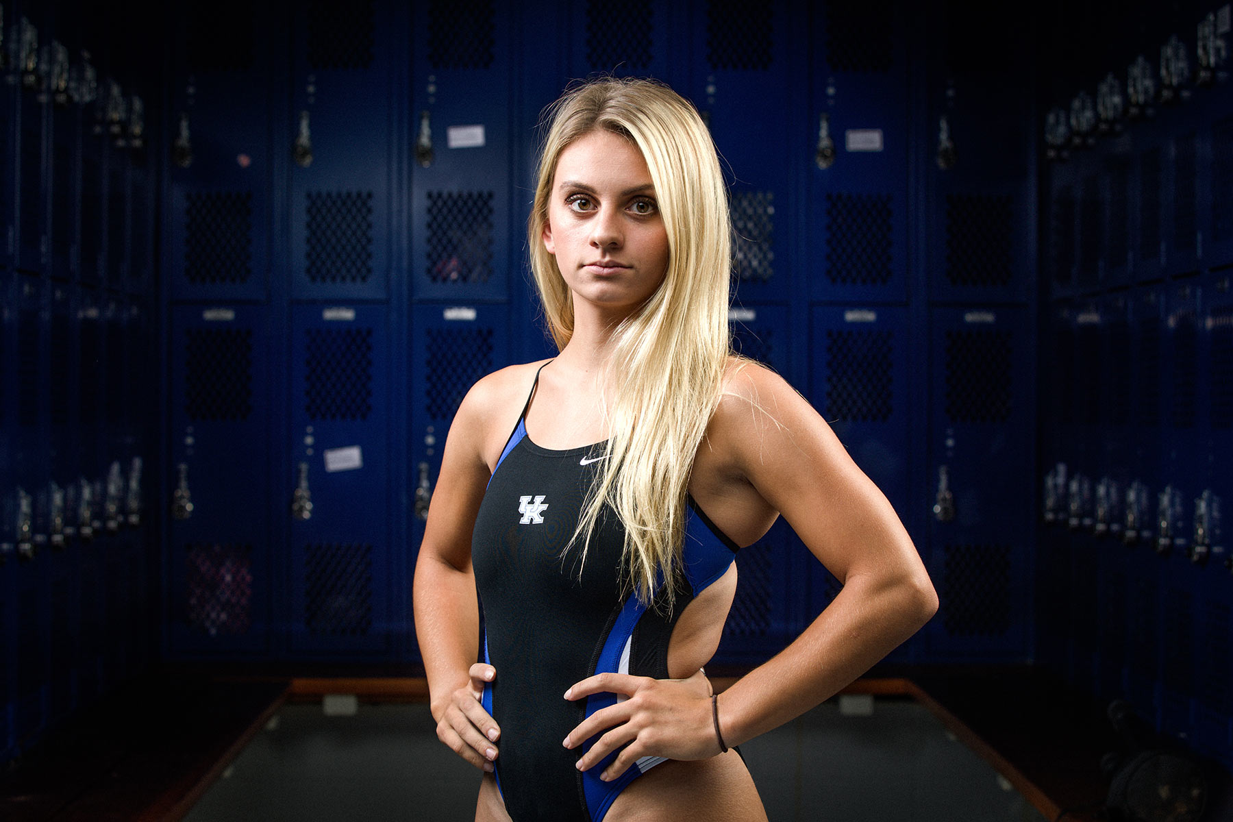 Emma, wearing a blue and black UK one-piece swimsuit, stands with her hands on her hips. She's in a blue locker room and looks strong.