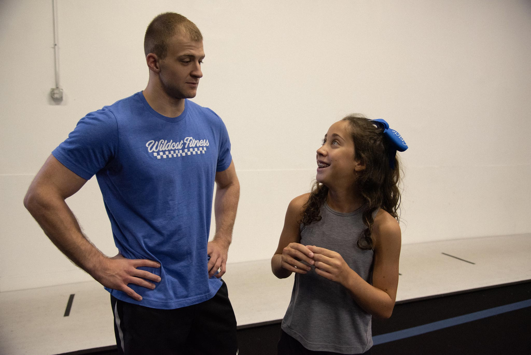 Gracie pictured with a young adult male in a gymnasium after practicing cheerleading stunts. She is looking up at him and smiling.