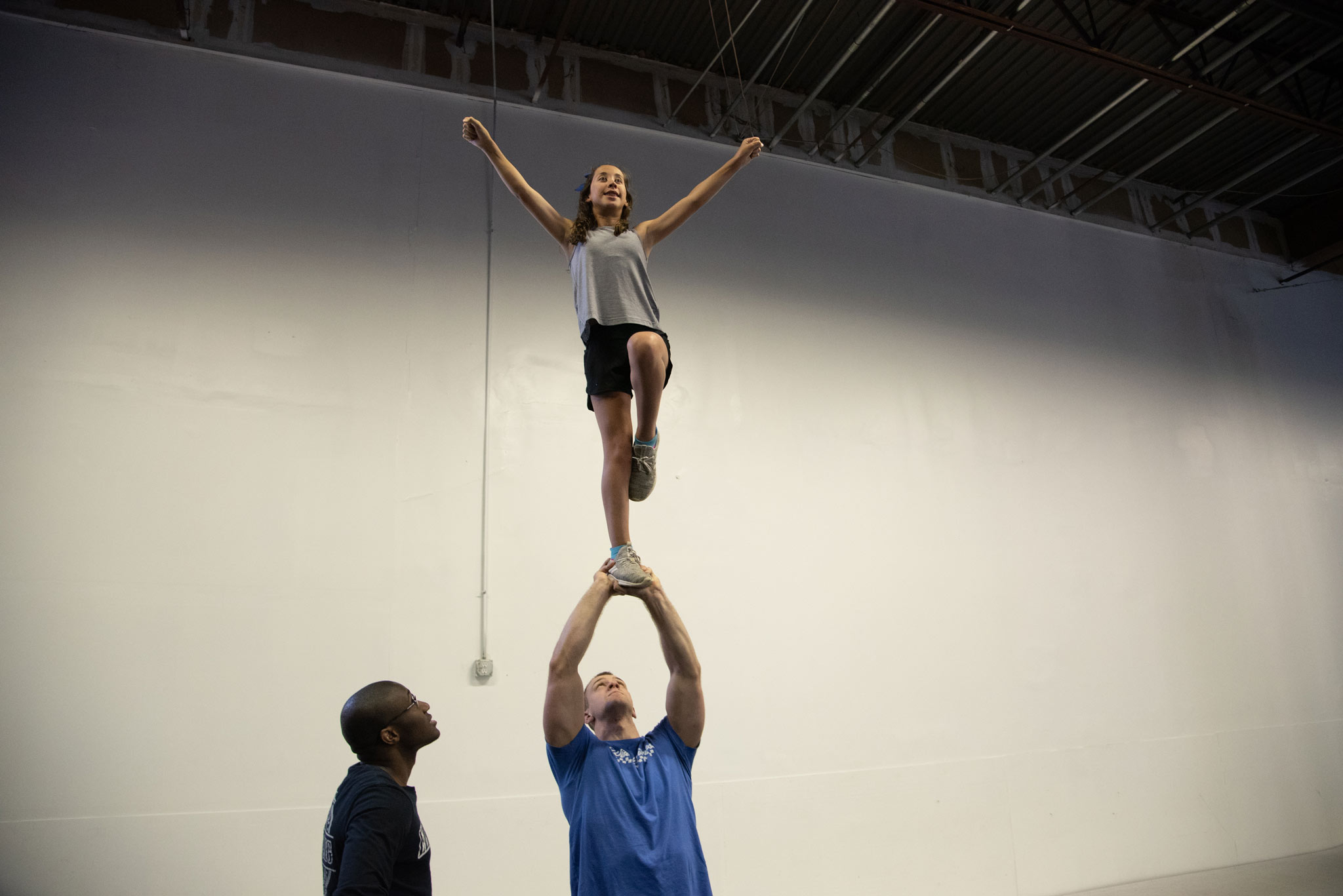 Gracie is lifted into the air by a young adult male practicing a cheerleading stunt. Her arms are raised and she is smiling.