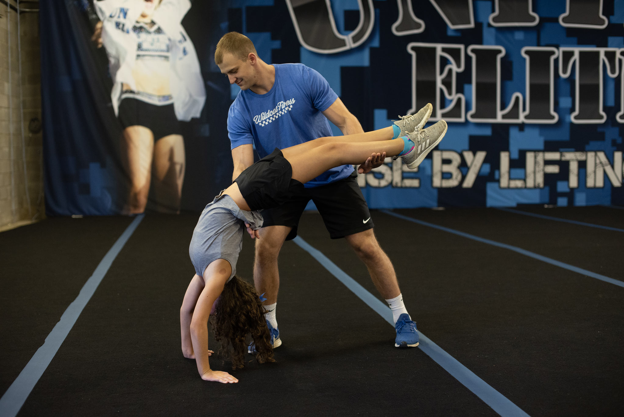 Gracie, a high school age girl with brown hair, practicing a back handspring with the help of a tall young adult male.