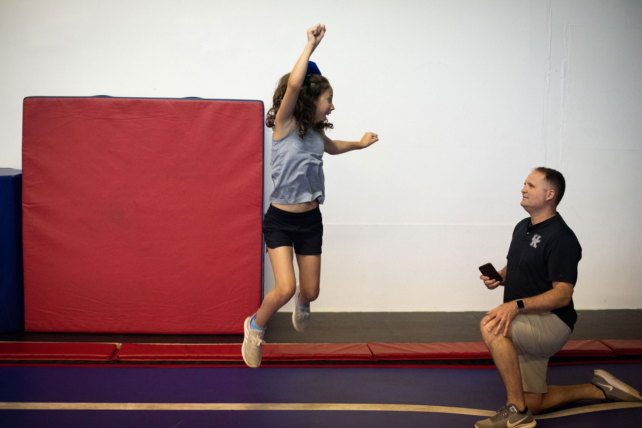 Gracie jumps enthusiastically on a gymnastics mat while her father, a middle aged man in a black polo shirt, watches her.