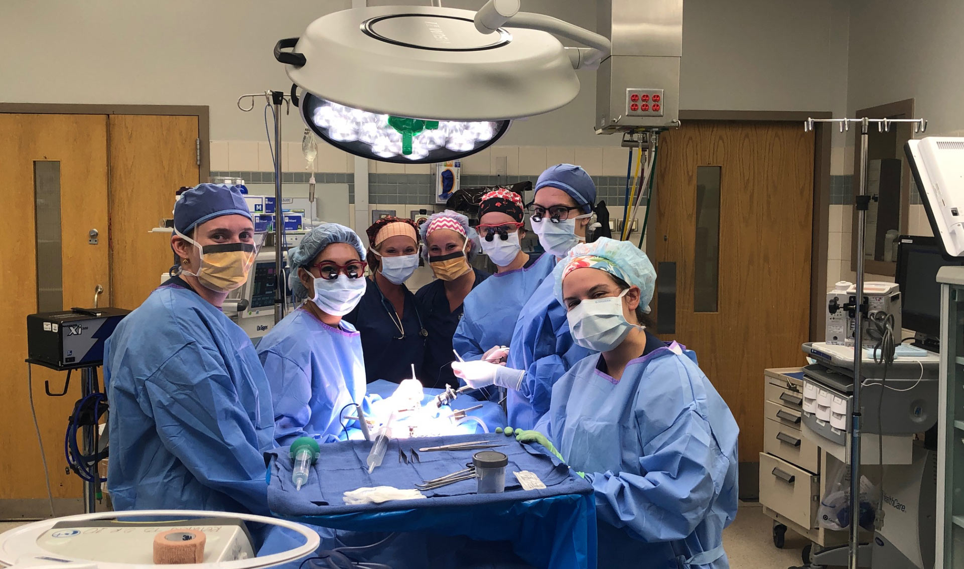 An all-female pediatric endocrinology team, all dressed in blue scrubs and surgical headgear with masks, circled around an operating table.