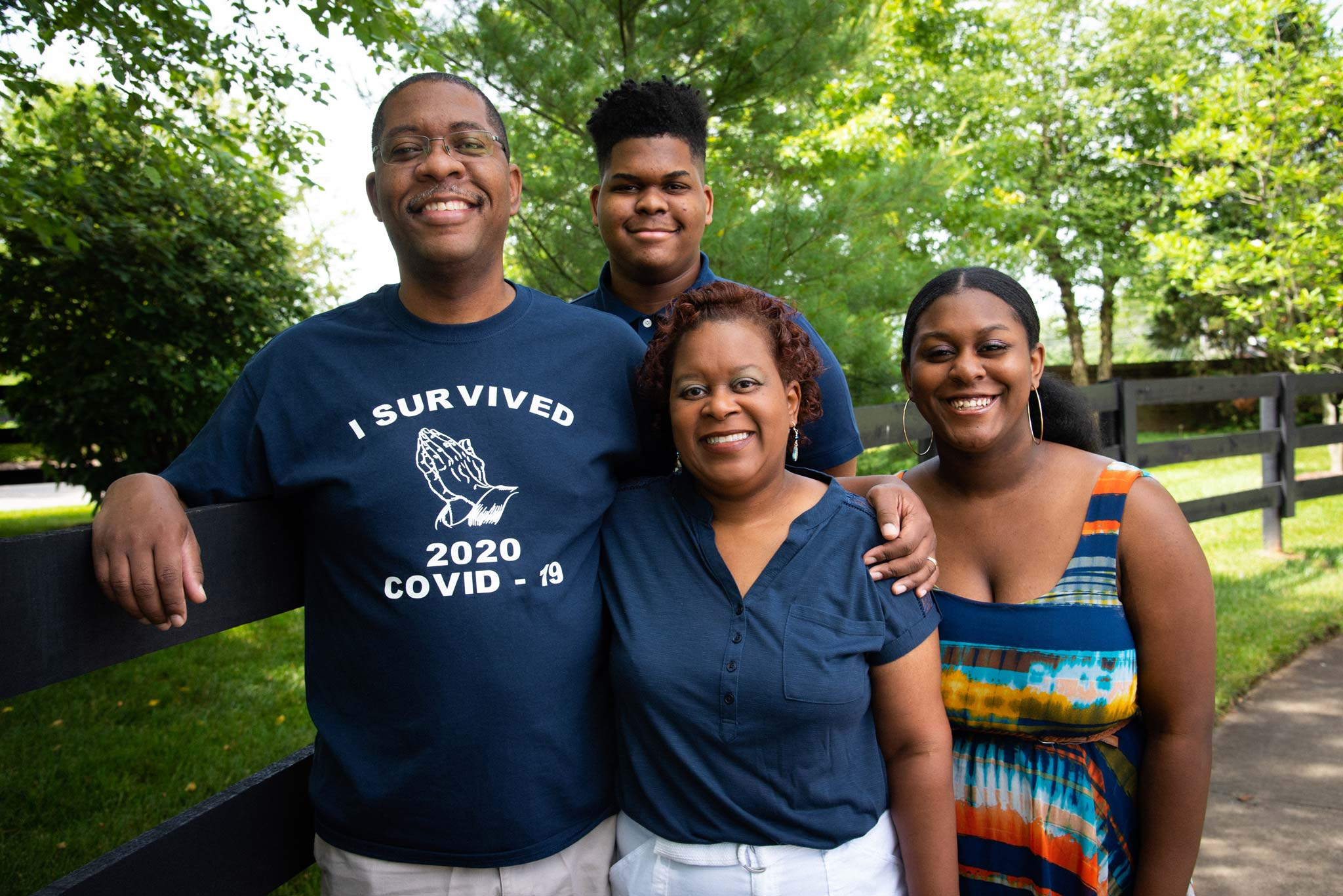 """The Johnnson family stands in front of a black plank fence. Jerome has his arm around Jeanine's shoulders. He is wearing a shirt that says """"I survived 2020 COVID-19."""""""