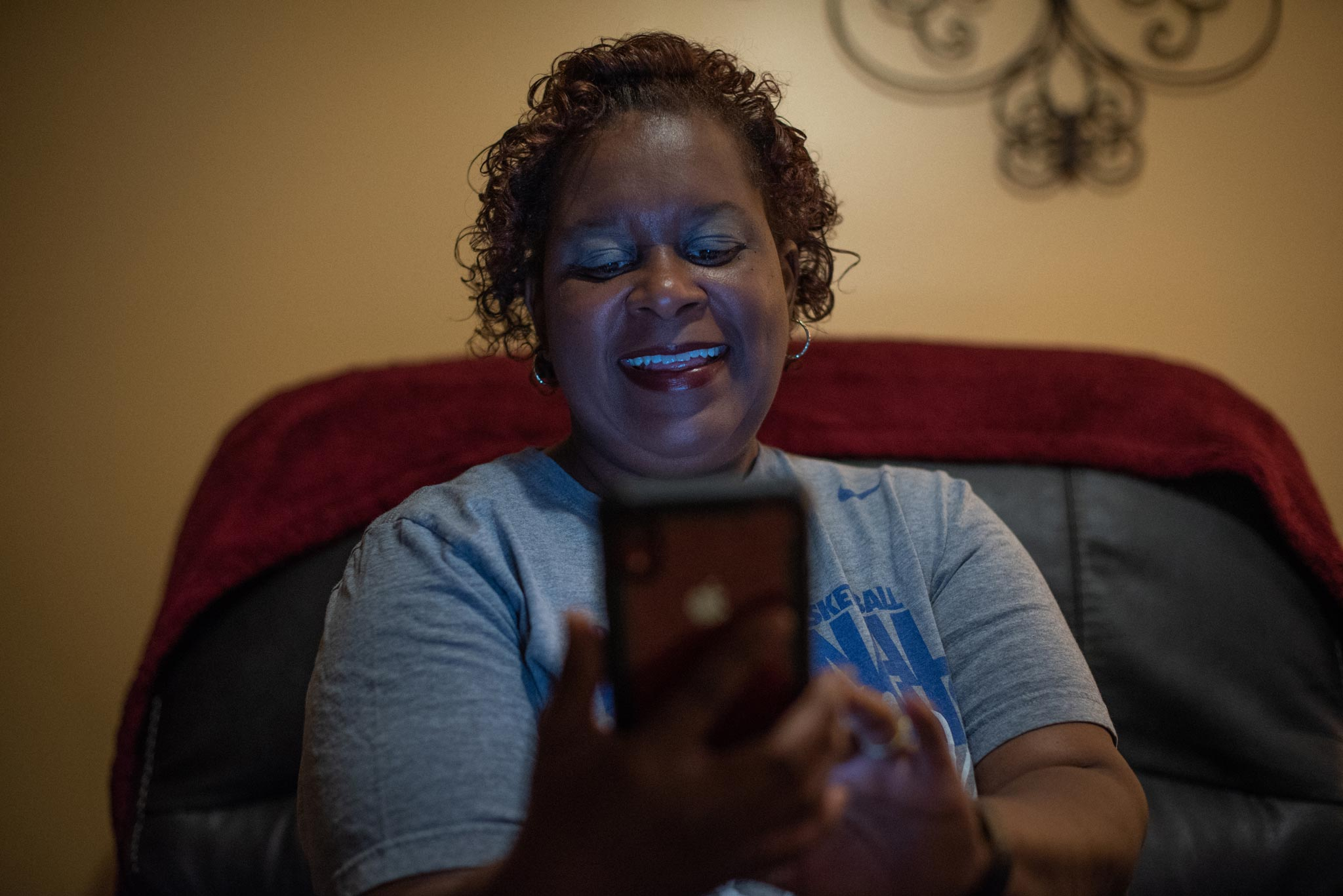 Jeanine smiles as she looks at her phone.