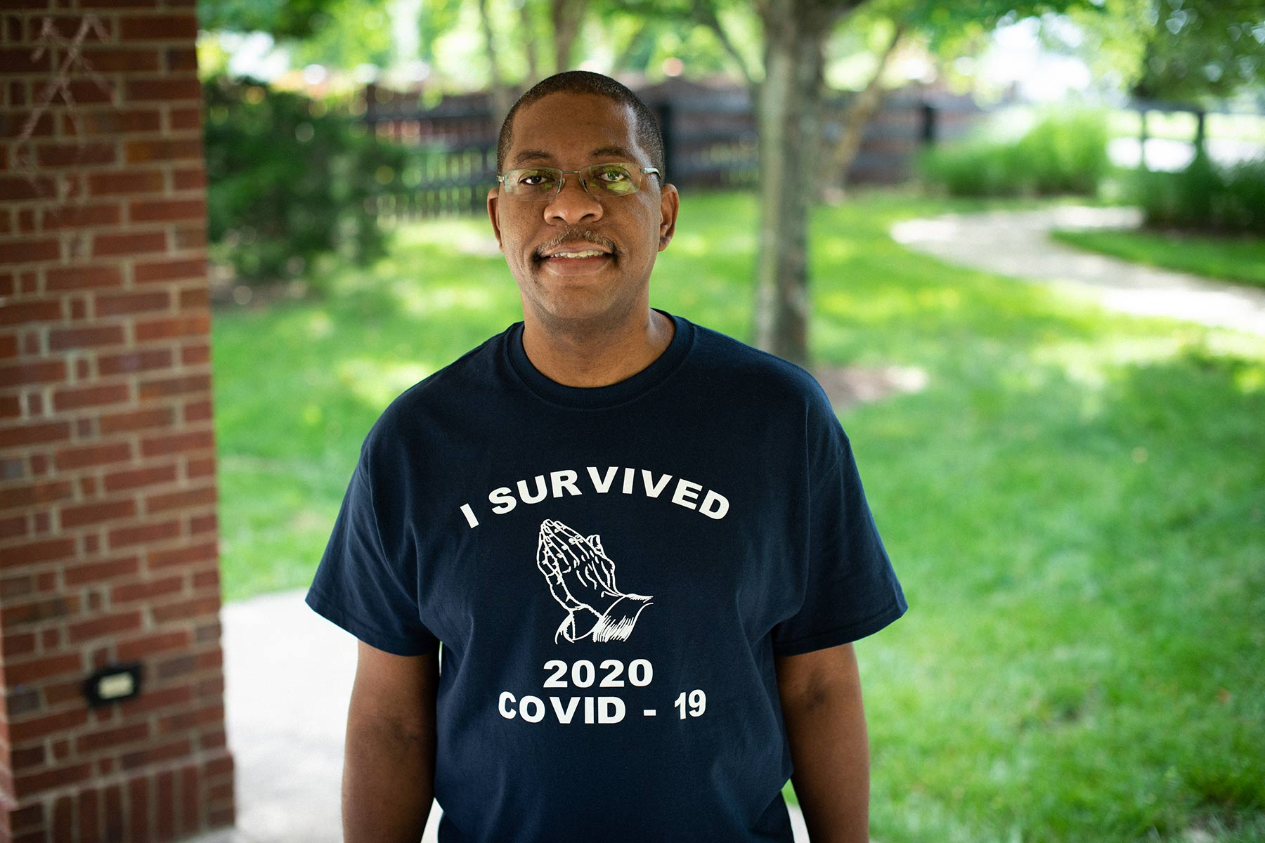 """Portrait of Jerome outside smiling while wearing a shirt that says """"I survived 2020 COVID-19""""."""