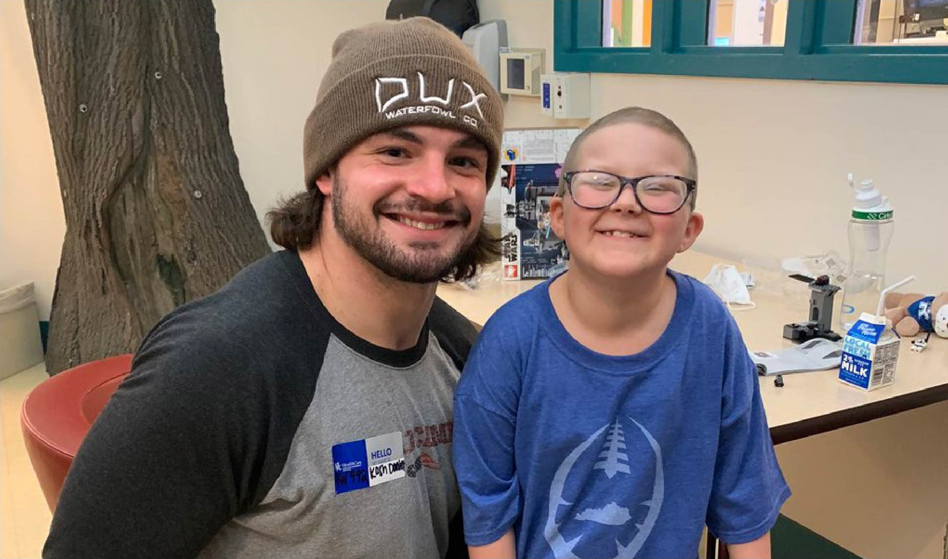 Kash Daniels, a football player, poses for a picture next to a little girl, Ellie. Ellie has buzzed hair and glasses. Kash is wearing a brown toboggan. Both are smiling.