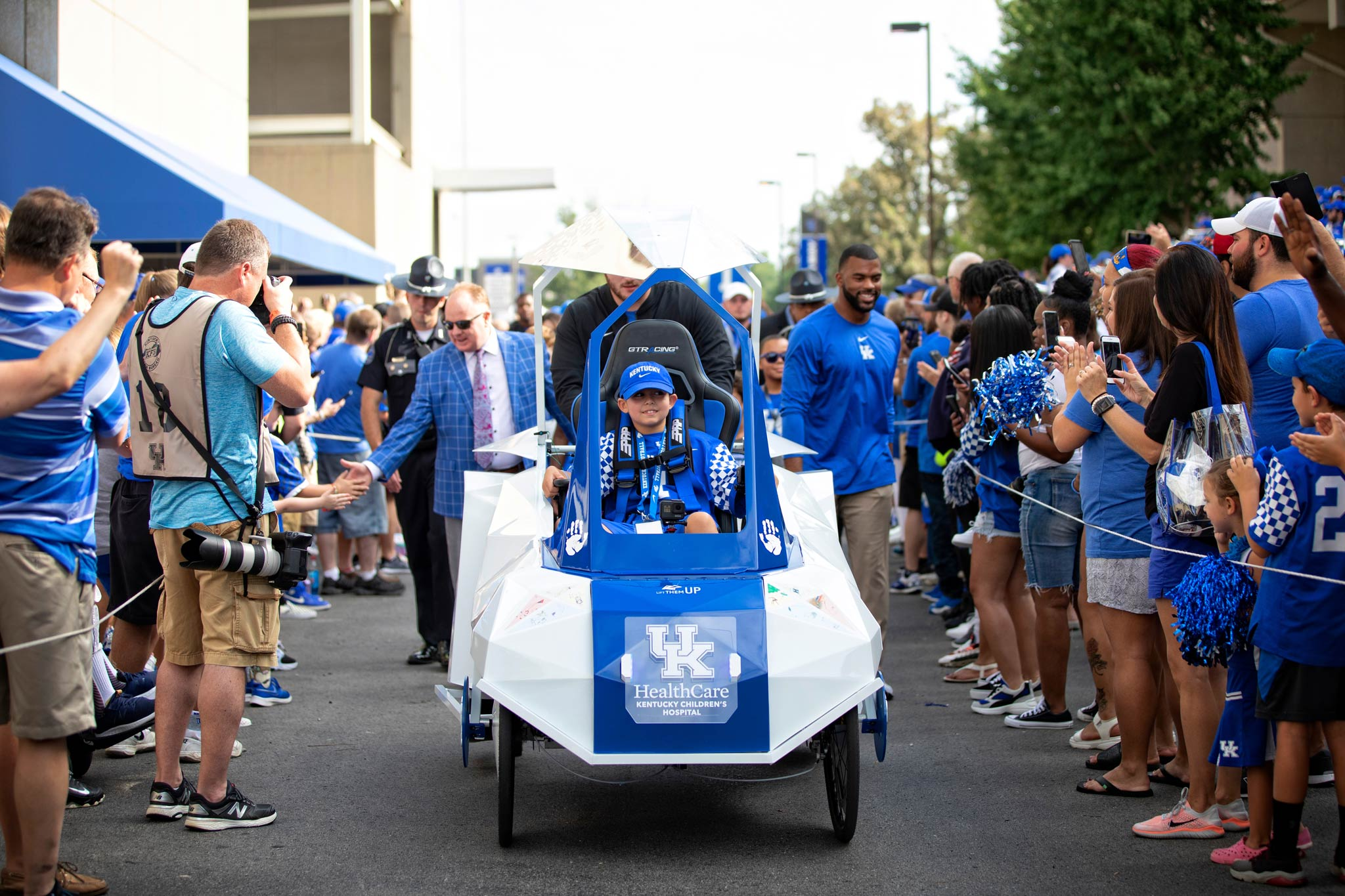 A little boy, riding in a futuristic-looking cart, leads Coach Stoops, Courtney Love, and the football team through a crowd of fans.