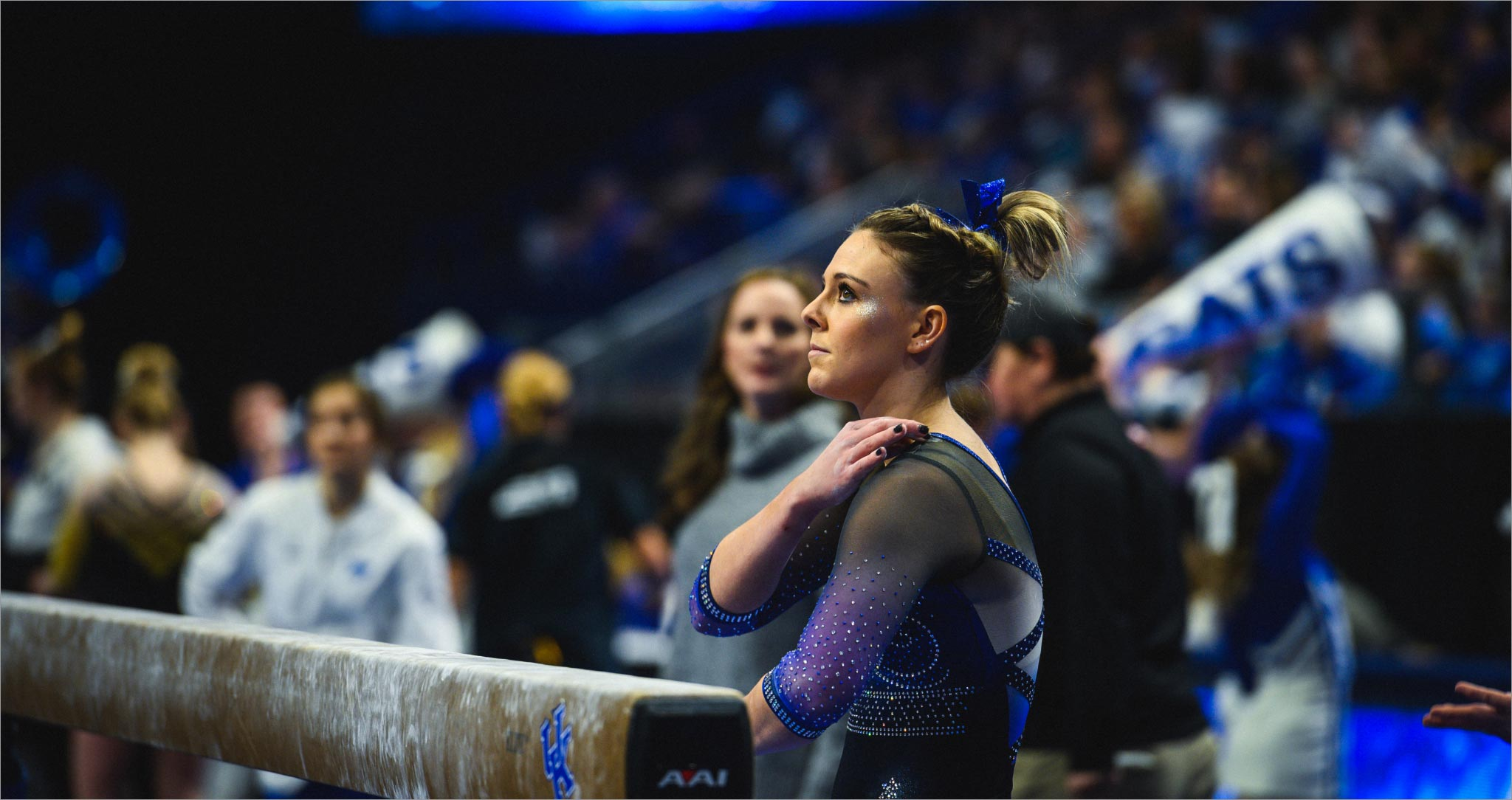 Mac, wearing a sparkly blue, black and white leotard, looks up at something outside of the frame. Her brown hair is up in a bun and has a blue ribbon in it. We can see a blurry crowd behind her.