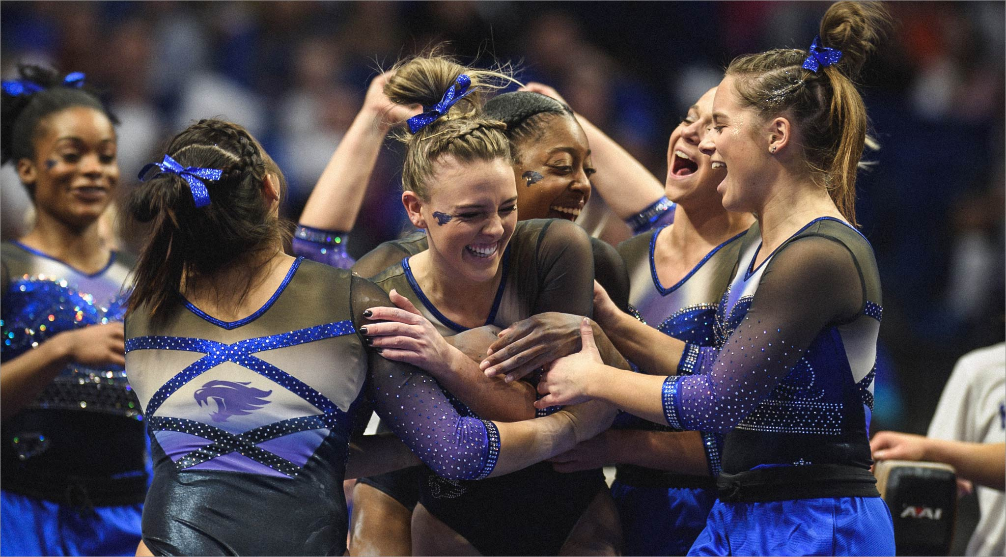 Mac celebrates with a group of very excited gymnasts, all wearing matching blue and black leotards. They are all smiling, jumping, and hugging Mac.