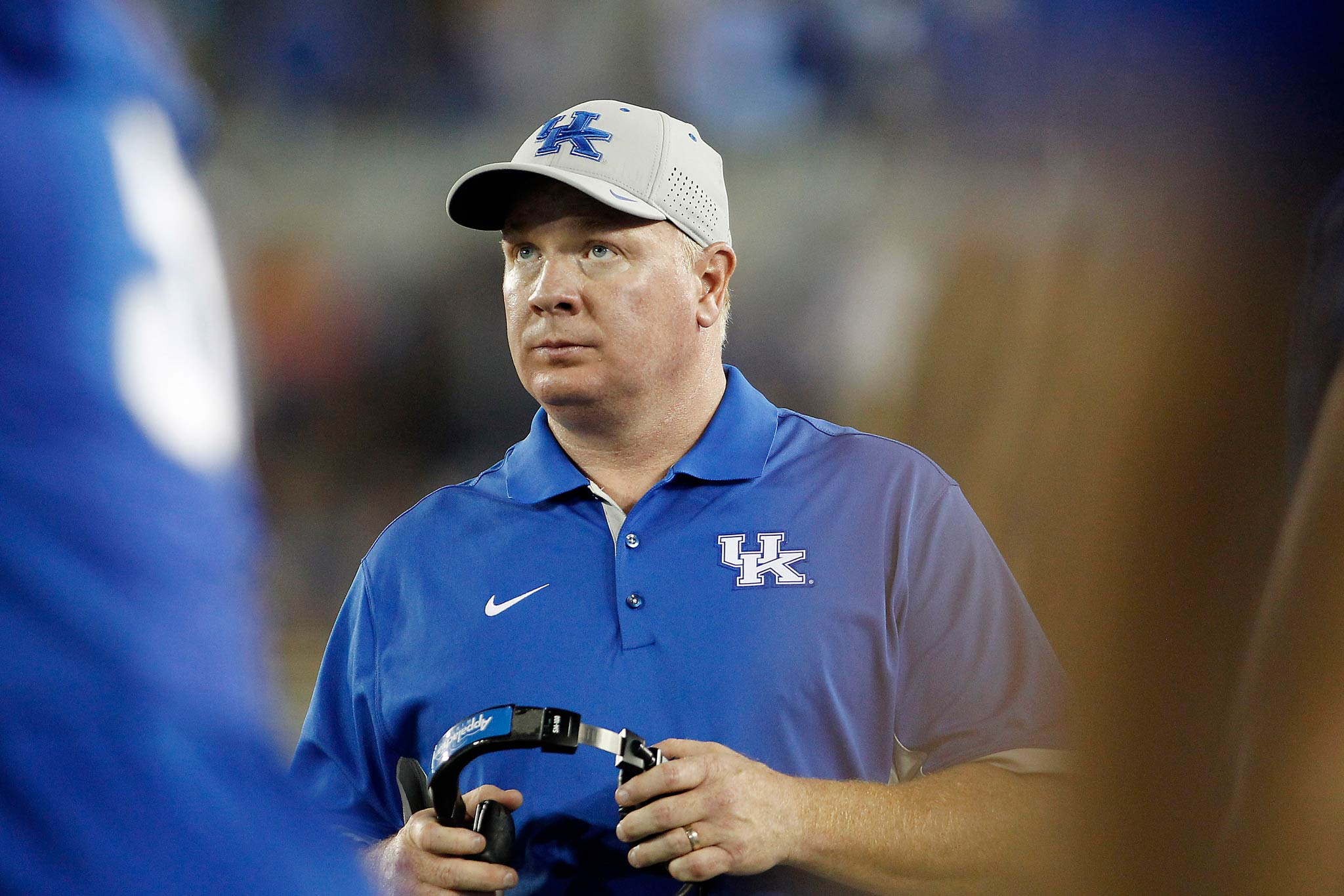 Coach Stoops, holding a headset, looks up during a game. He is wearing a blue UK polo shirt and UK baseball cap. The background and foreground are both blurred.