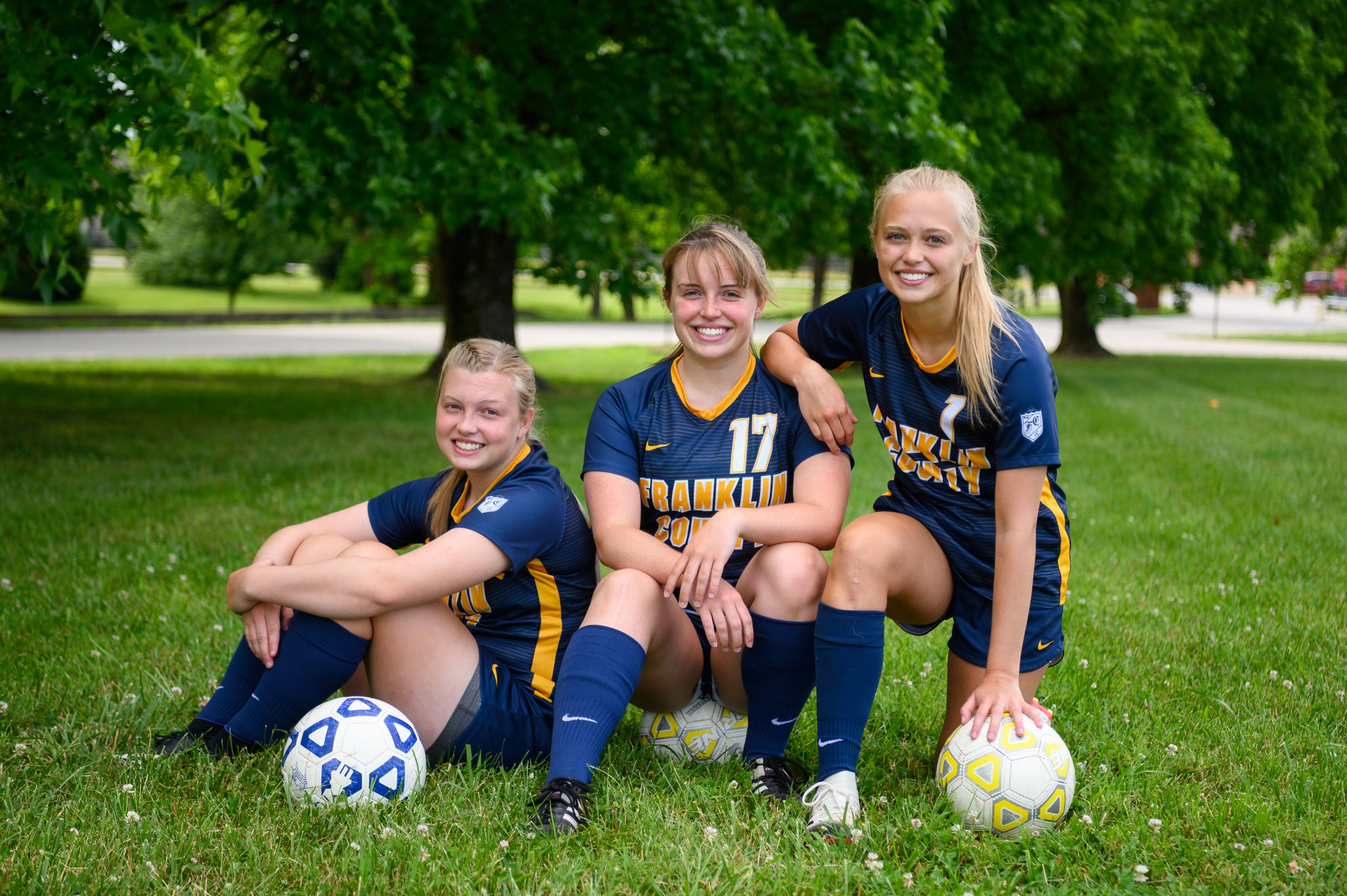 The three girls together crouching down on the field, each with a soccer ball, smiling.