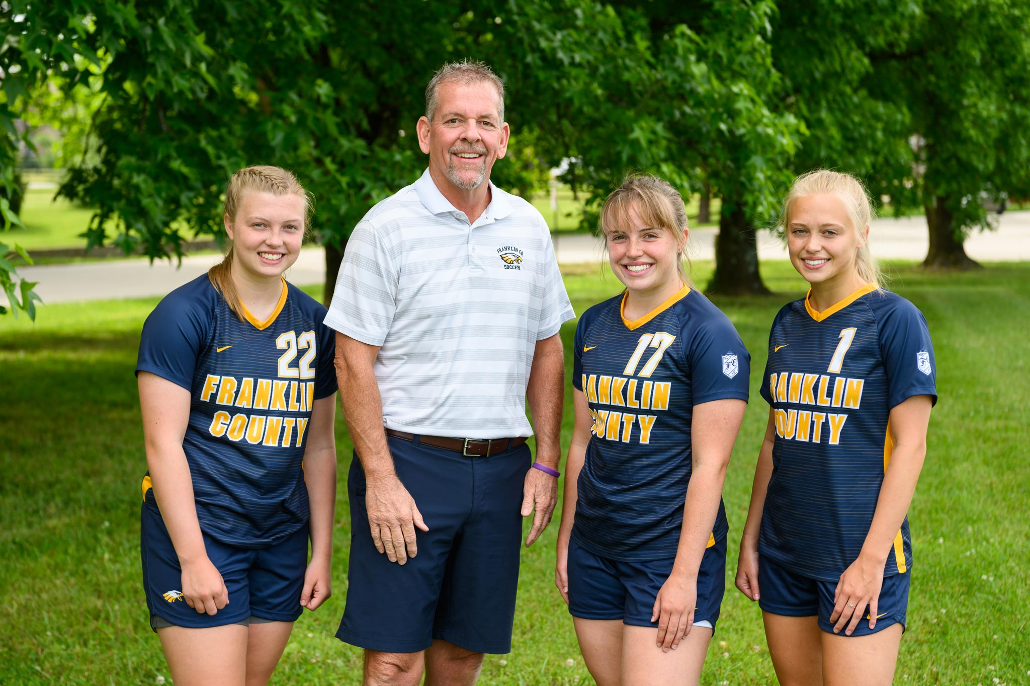 The three girls pose smiling with Coach Jon Sutphin, a tall middle aged man with a beard.