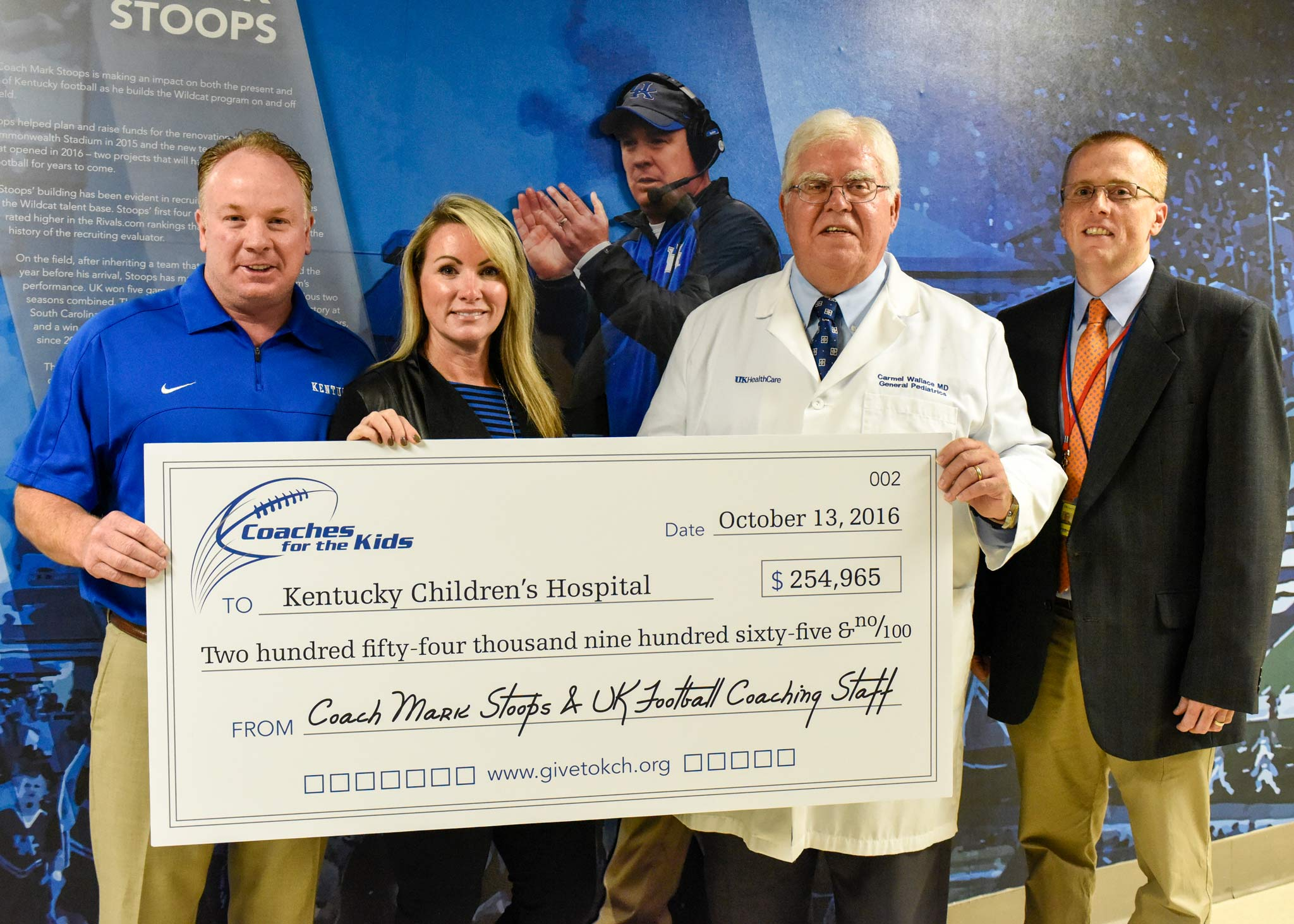Mark and Chantel Stoops present an oversized check for $254,965 to two doctors from Kentucky Children's Hospital.