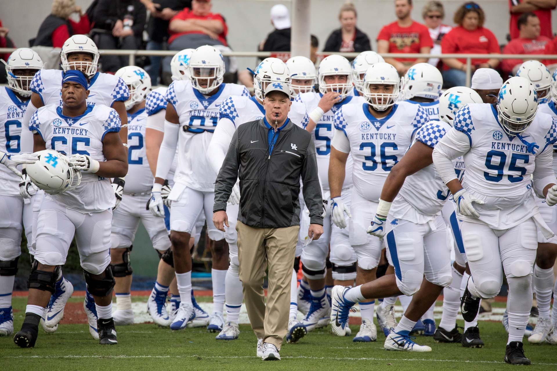 Coach stoops, wearing a gray jacket, leads a team of Kentucky football players onto the field. He has a whistle in his mouth and is wearing a UK baseball cap.