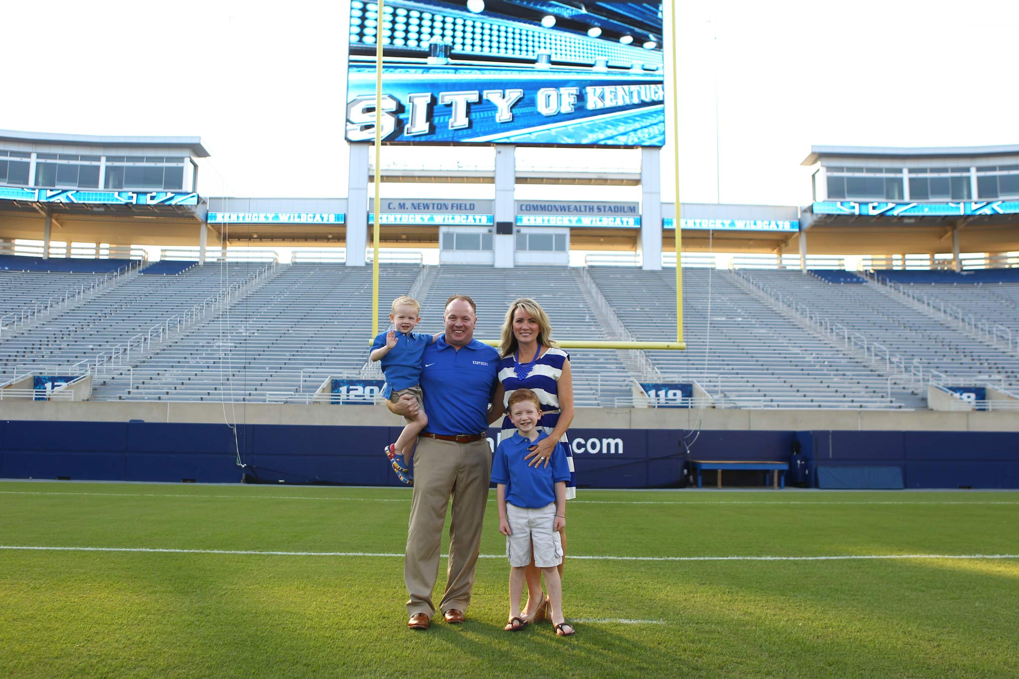 Coach Stoops stands with his wife and sons in front of the goal at Kroger Field. They are all wearing blue.