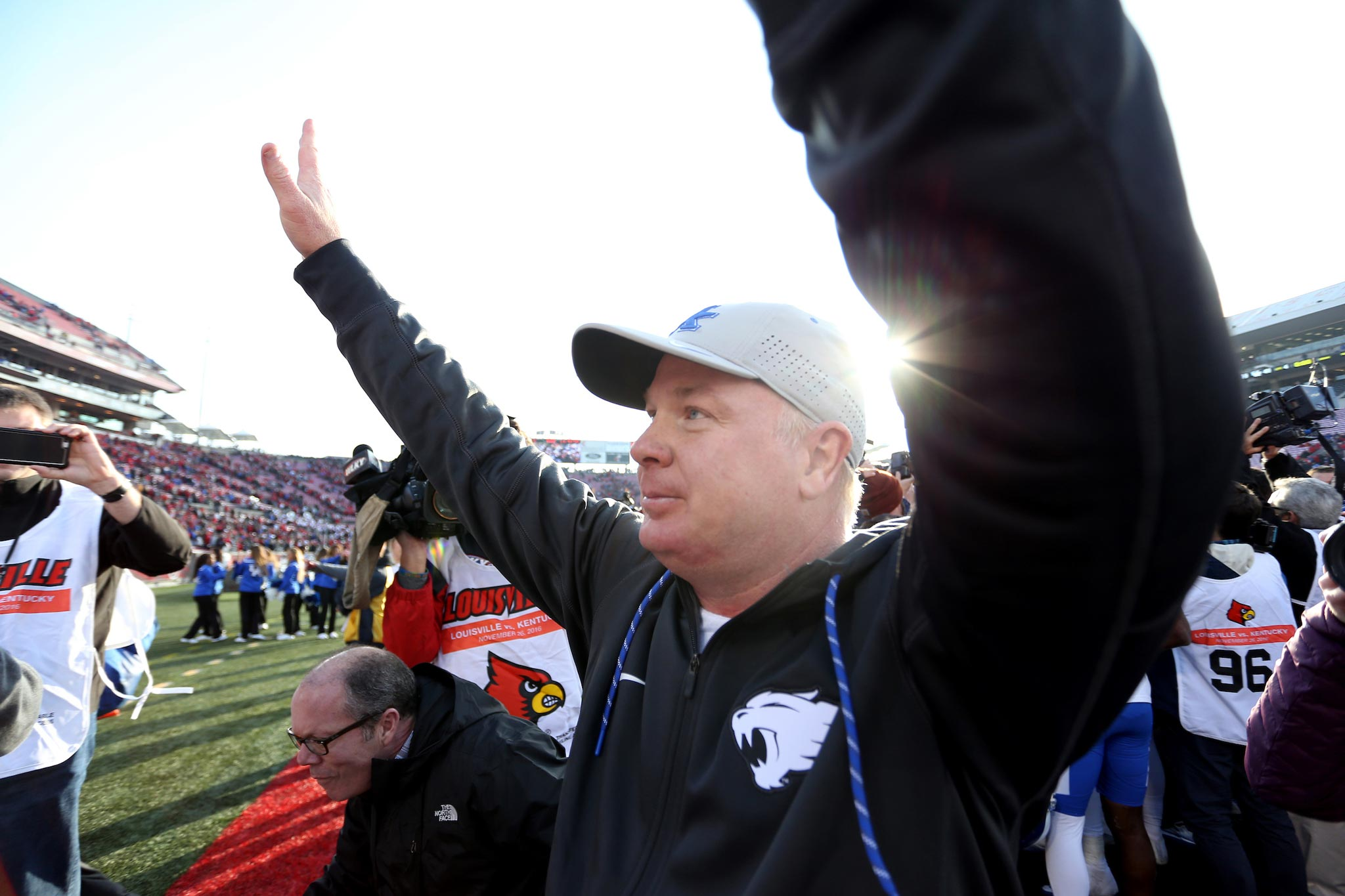 Coach Stoops, standing on the sidelines at a game, looks out onto the field and raises his hands above his head. He is wearing a black Wildcats jacket and a white UK hat.