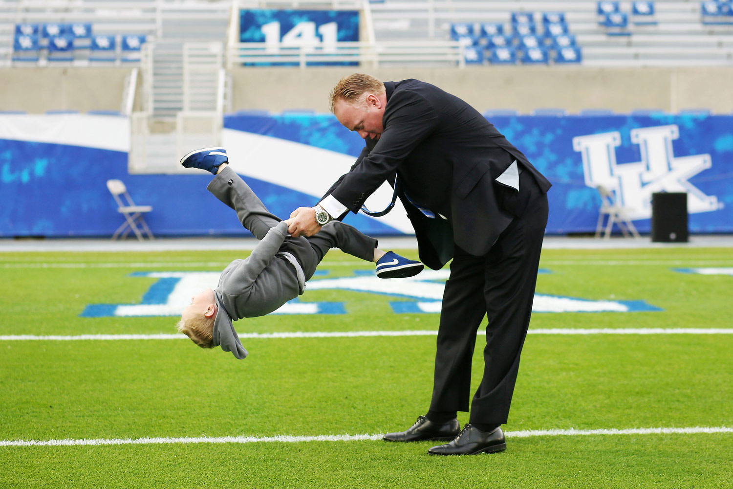 Coach Stoops, wearing a suit, holds his son's hands as his son flips through Coach's arms. His son is upside down, mid-flip, and is wearing a gray sweatshirt gray pants and blue sneakers.