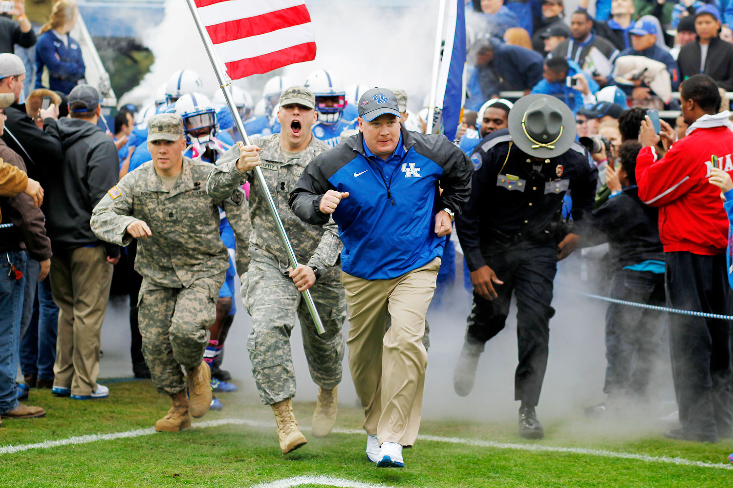 Coach Stoops runs out onto the field ahead of two National Guardsmen in uniform, one holding a flag, as well as another uniformed person. The football team is behind them.
