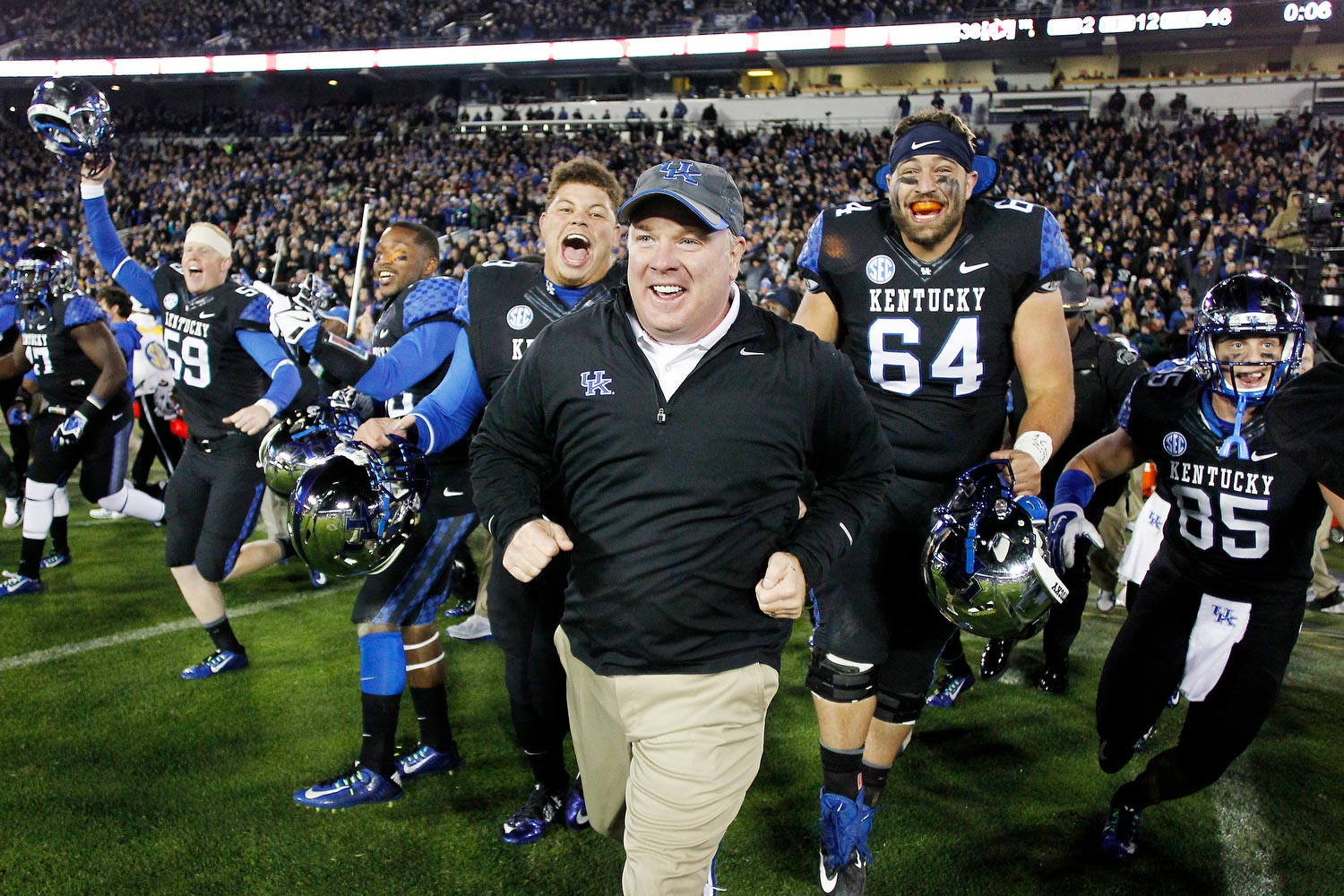 Grinning broadly, Coach Stoops runs out onto the field after a victory. He's surrounded by extremely excited Kentucky football players.