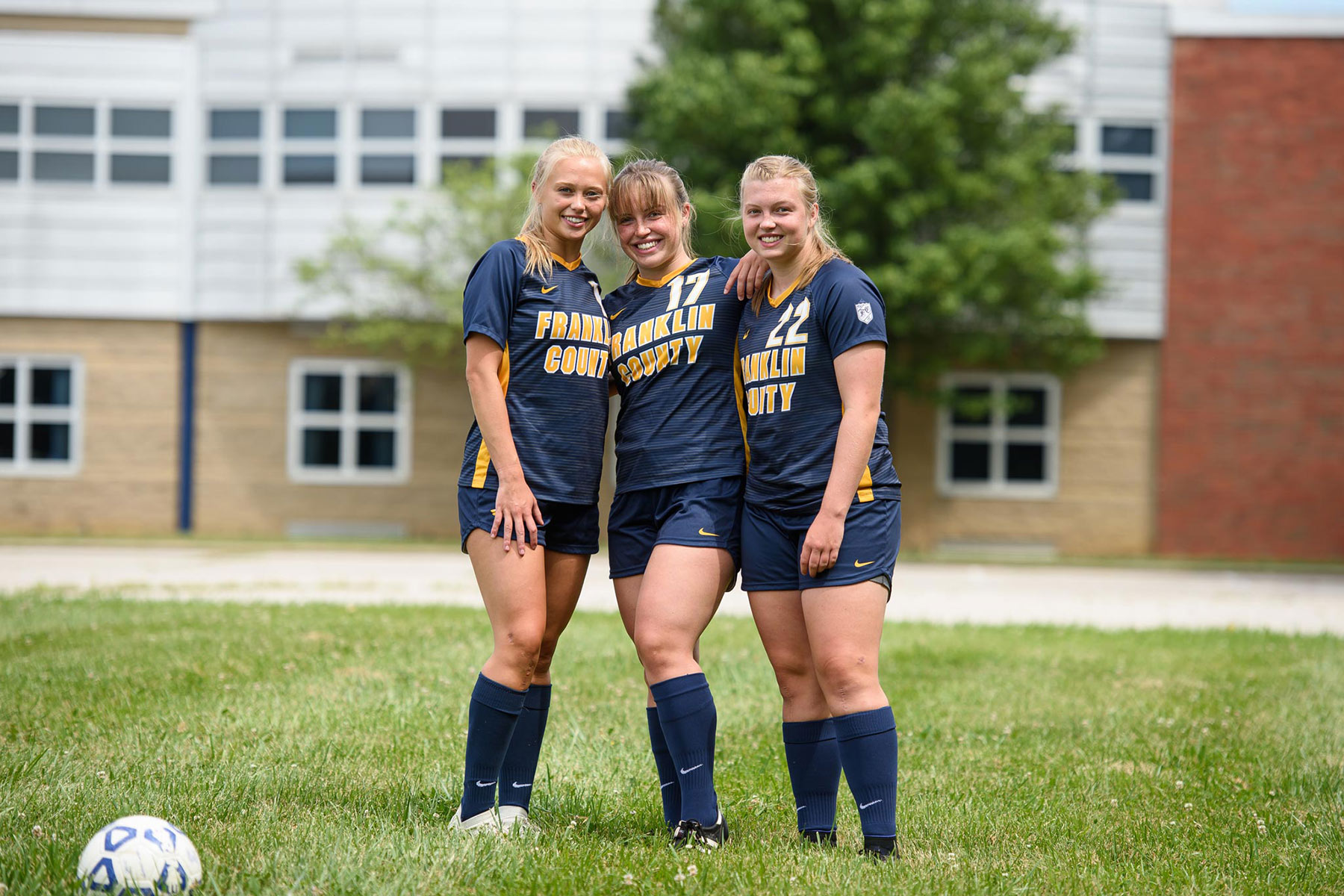 The three sisters stand close together for a group photo in their soccer uniforms.