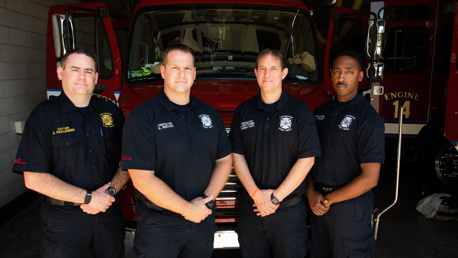 Four adult men in EMS and Fire Rescue uniforms standing with their hands clasped in front of a fire engine.