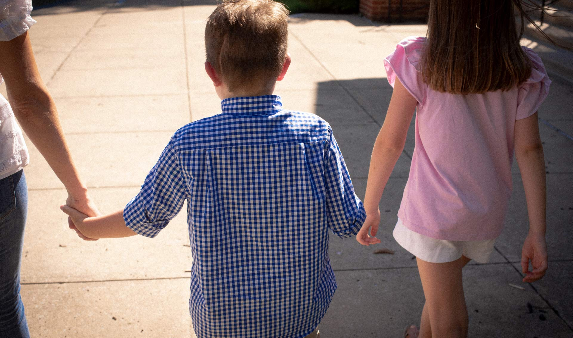 A photo from behind Elliott as he walks in between his mother and sister holding both of their hands.