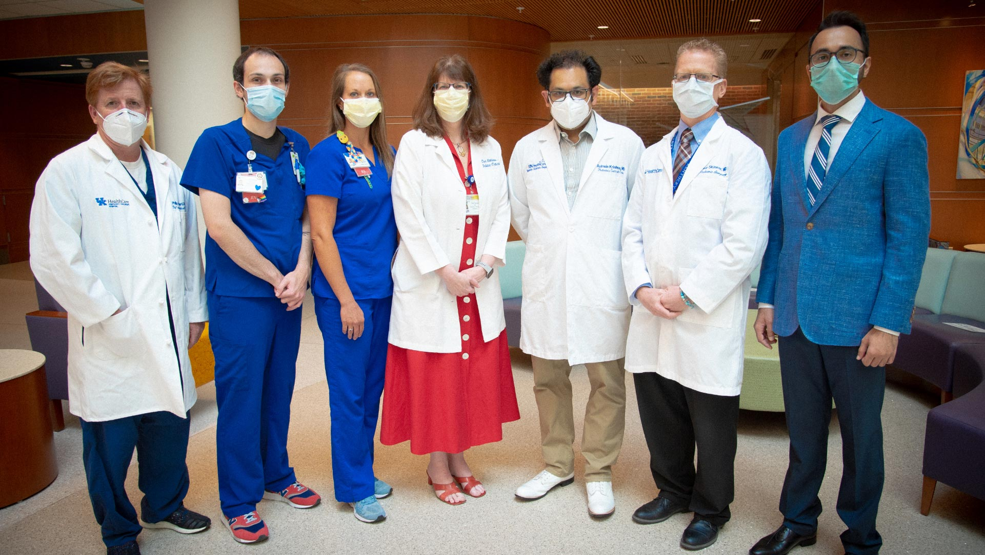 A group of doctors, nurses and therapists stand in a line formation for a portrait photo.