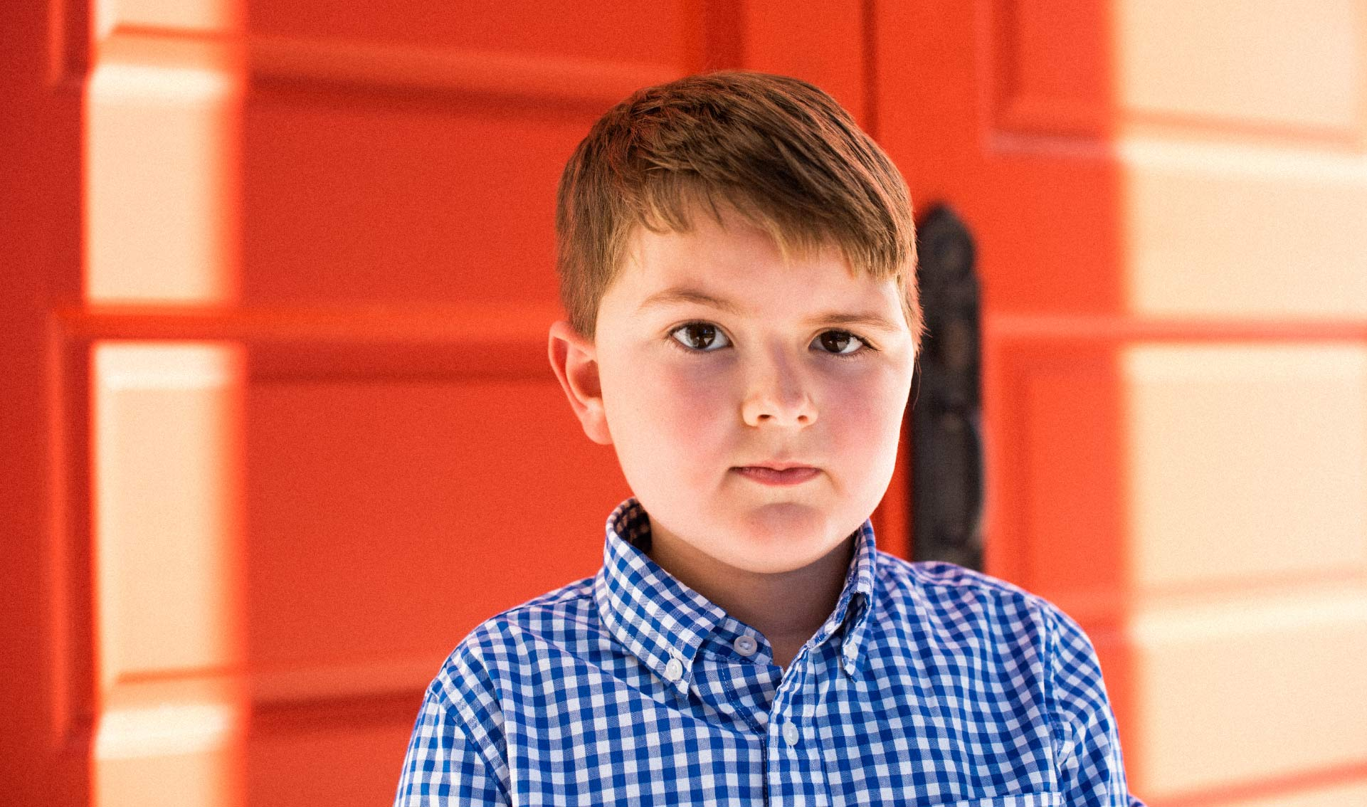 Elliott, a young boy in a blue and white checkered shirt, looking into the camera and slightly smiling.