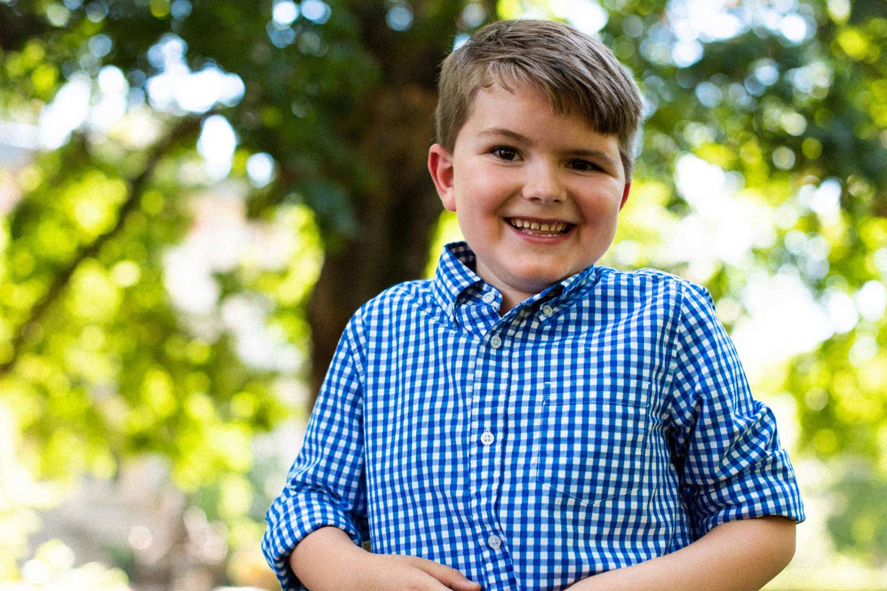 A close up portrait of Elliott, a young boy wearing a blue and white checkered shirt, smiling into the camera while tilting his head slightly.