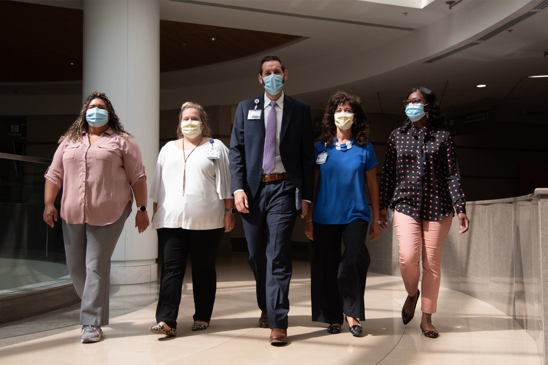 A group of people walking side by side down an open hallway, all wearing face masks.