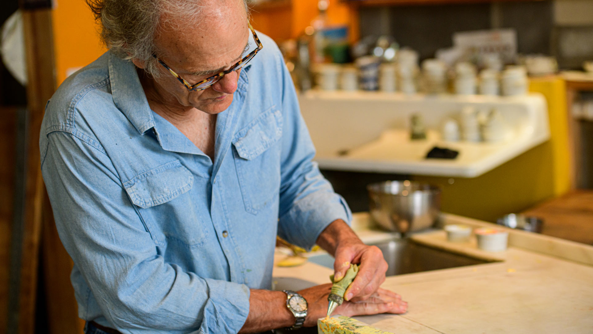 Lynn Sweet, an older man with gray hair and horn-rimmed glasses, does some detail work on a painting. He is wearing a blue button-up shirt.