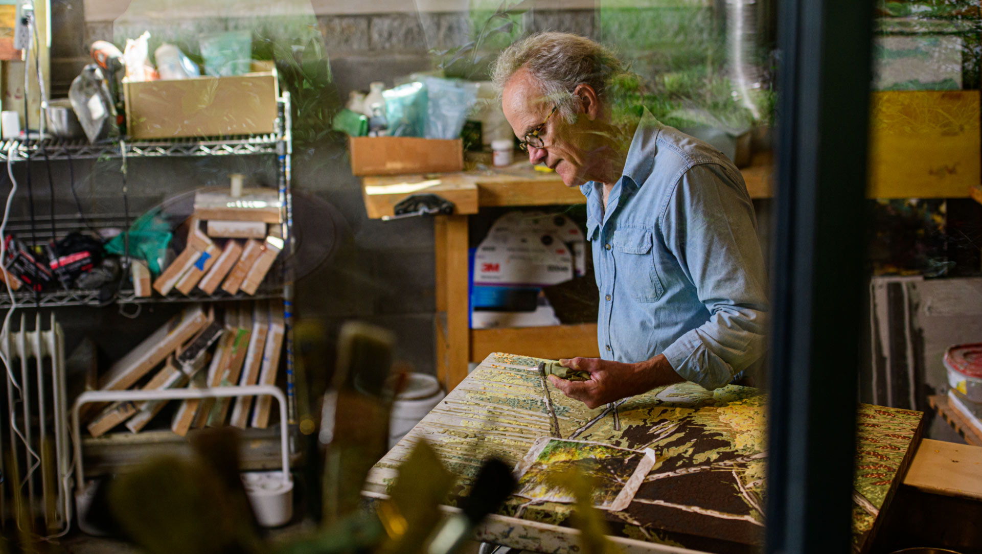 We see Lynn through the window to his studio, working on one of his frescoes.