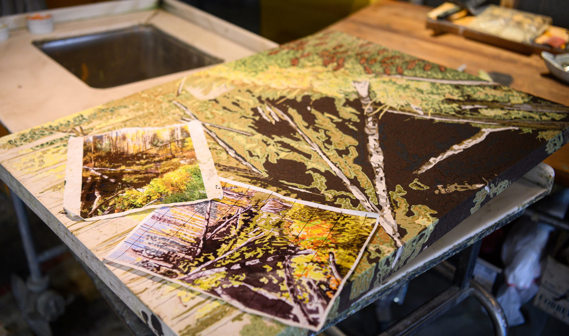 An in-progress painting on a work table, depicting abstracted trees and branches. There are two reference photos printed out and sitting on top of the painting, one covered with a grid.