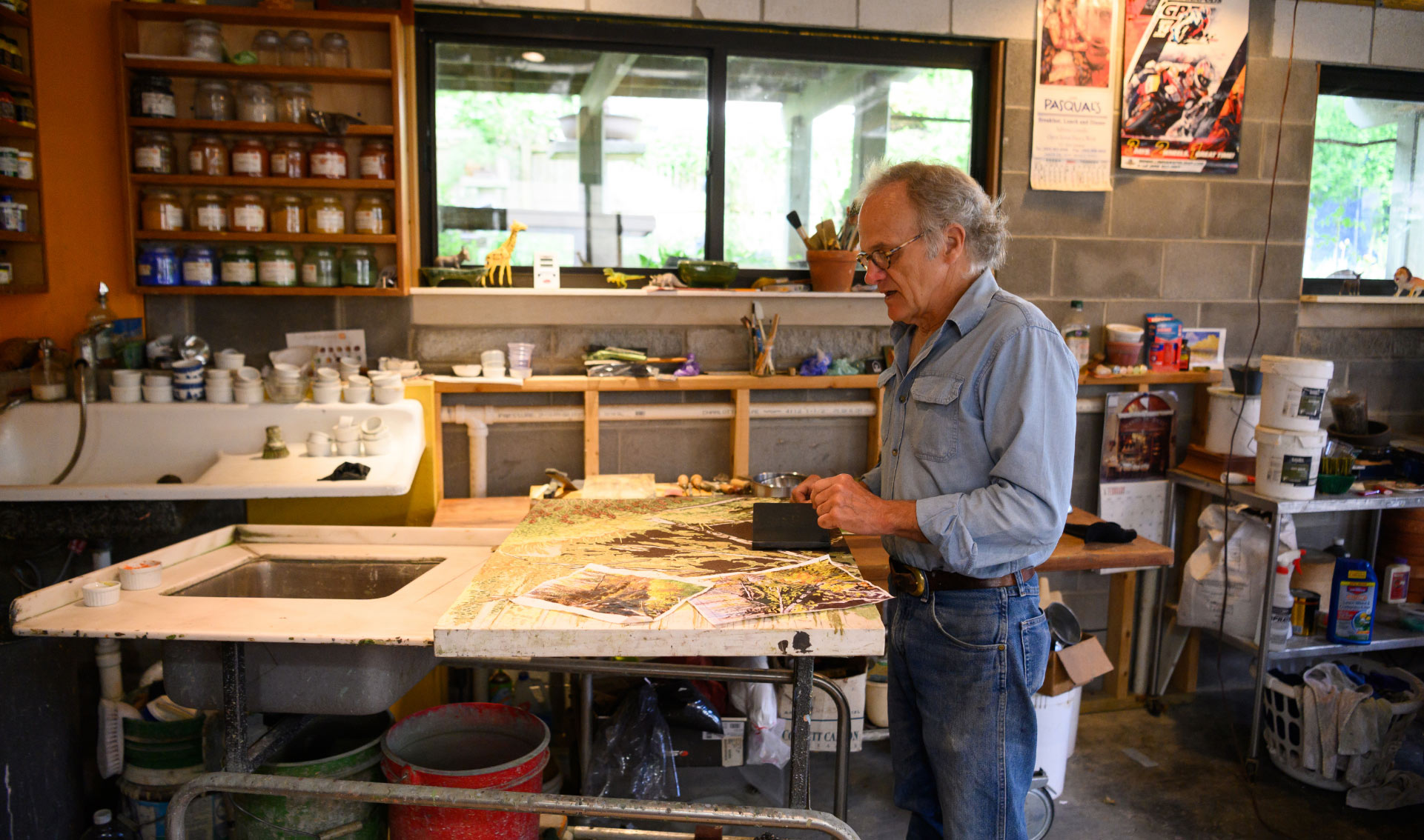 We see Lynn standing at a worktable in his studio in front of an in-progress painting. The painting has several reference photos on it.