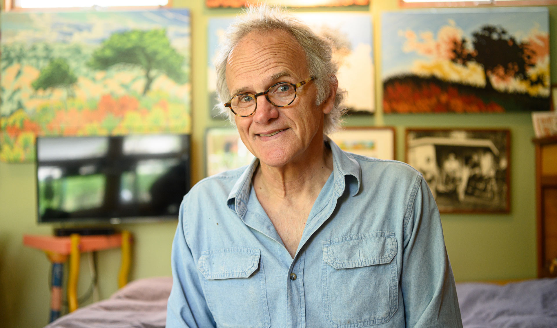 Lynn, smiling, stands in front of a wall of his paintings in his studio.