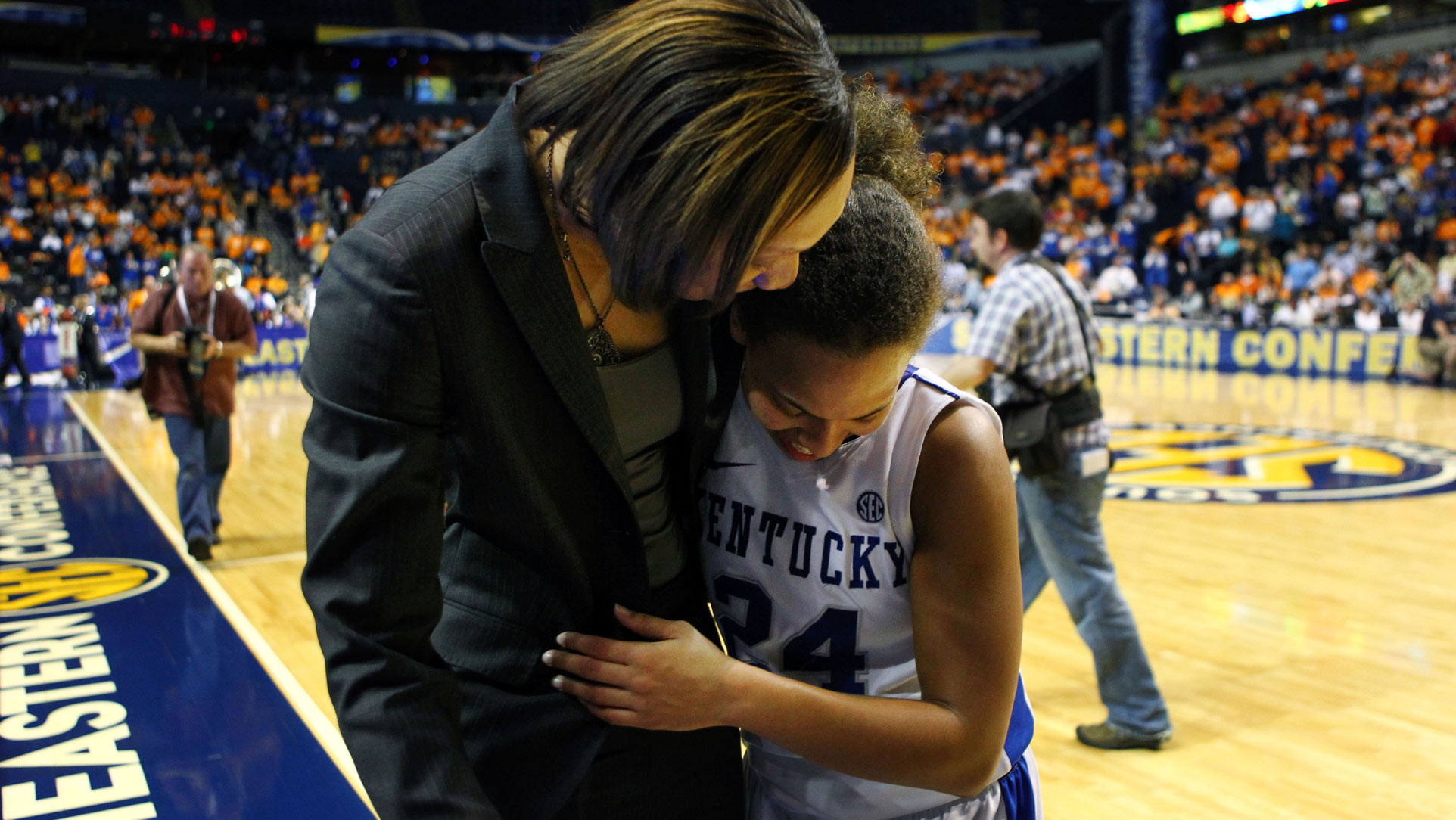A close-up photo of Amber, dressed in her game uniform, side hugging one of her coaches as they appear to talk on the sidelines of the court.