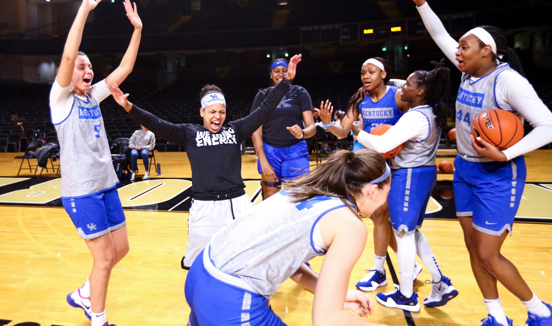 Amber and six of her teammates, all dressed in practice uniforms, celebrate and laugh together on the court.